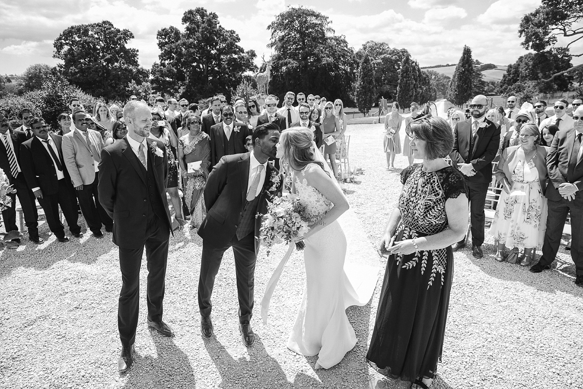 groom kisses bride as she reaches the end of the wedding aisle in outdoor ceremony at Pynes house