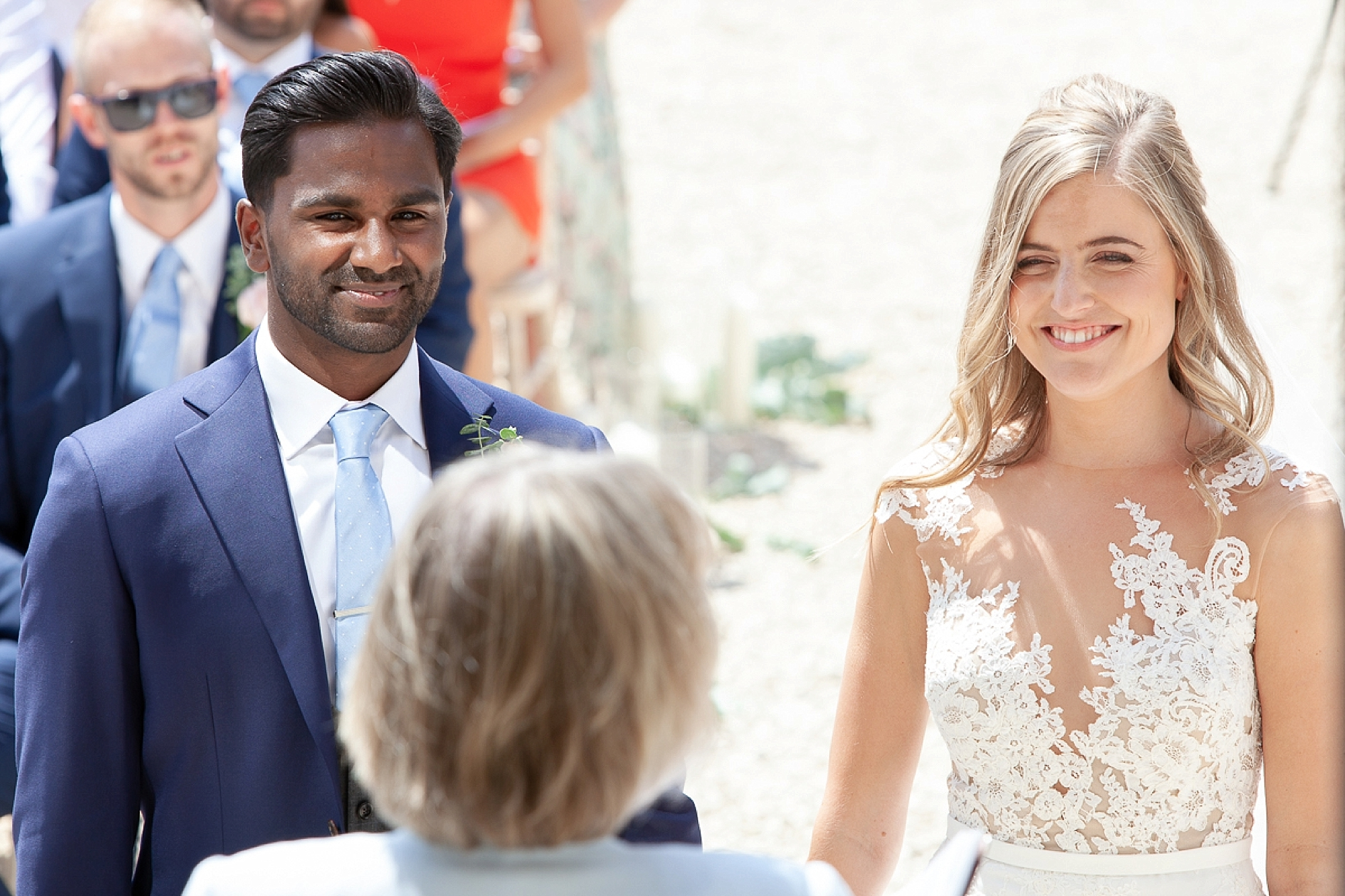 registrar stands in front of couple at Pynes house wedding in outdoors ceremony in devon