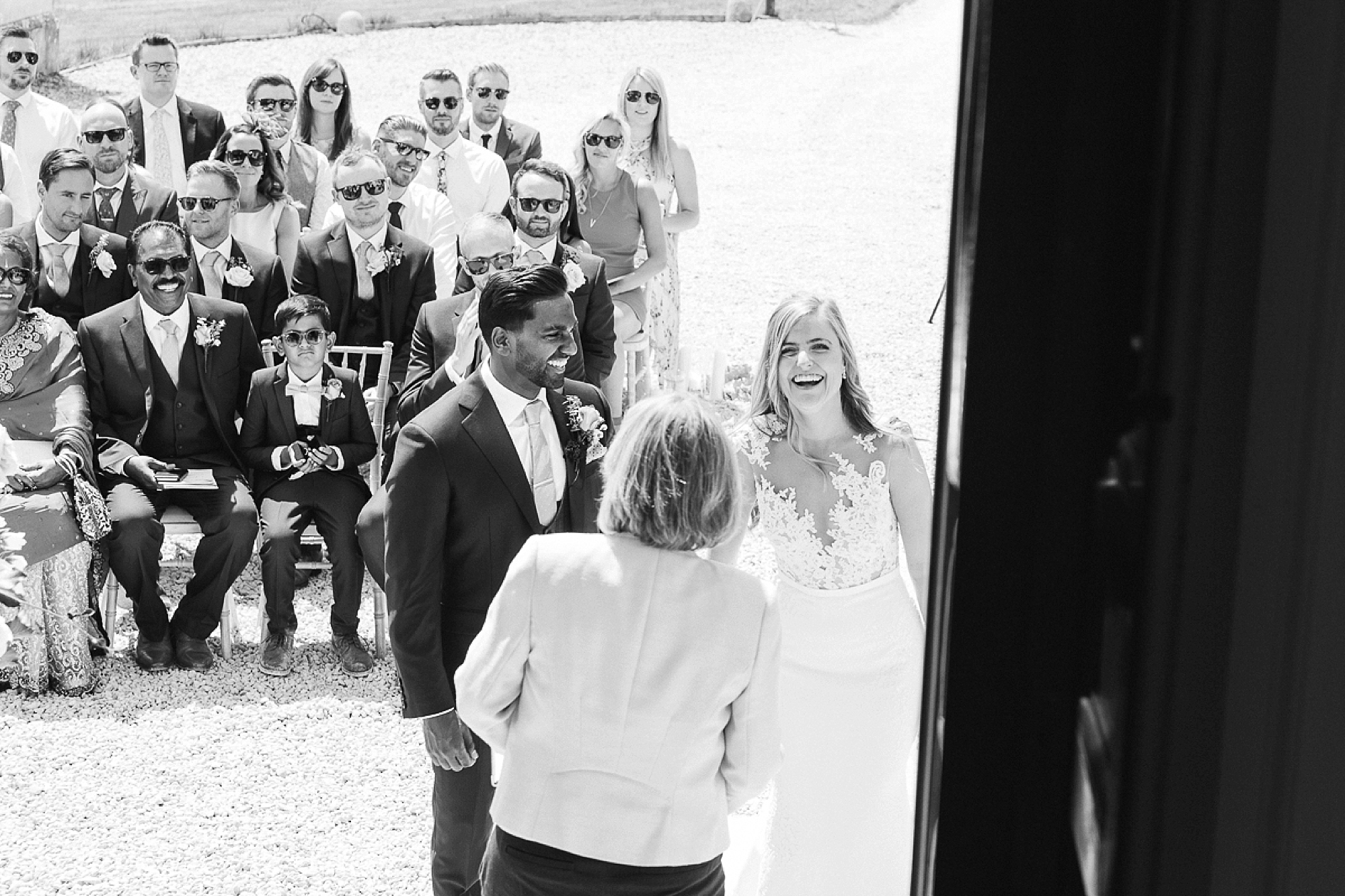 bride and groom with guests during outdoors wedding at Pynes House in black and white