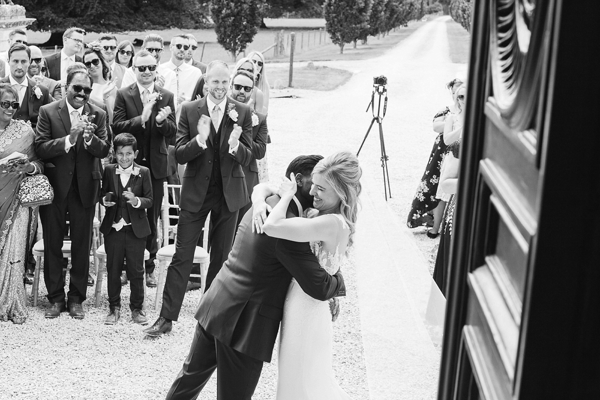 bride and groom hug at the end of their wedding ceremony as guests clap at Pynes House in Devon