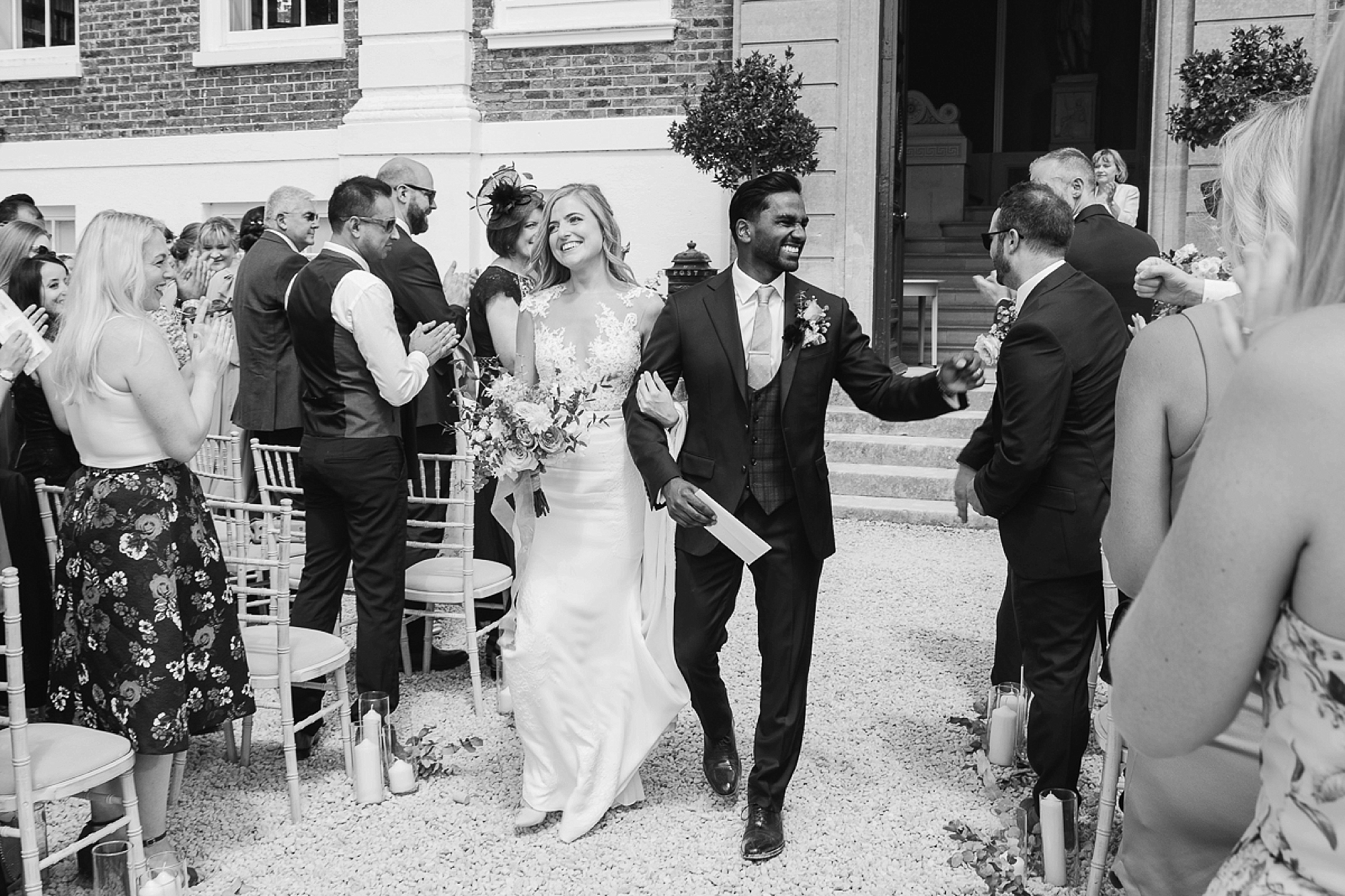 Bride and groom walk down the aisle at devon wedding in black and white