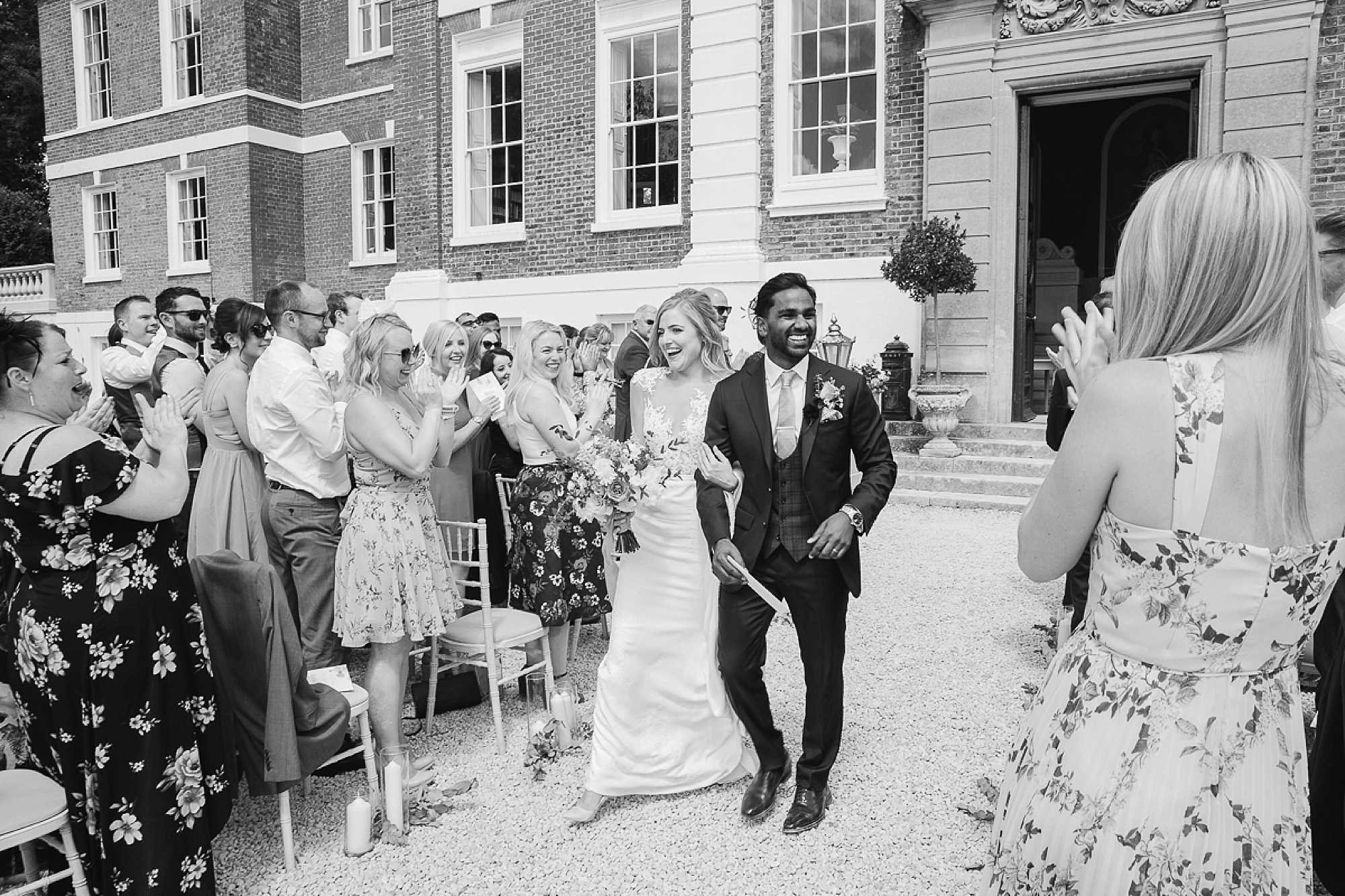 bride and groom laugh as they exit their Devon outdoor wedding ceremony