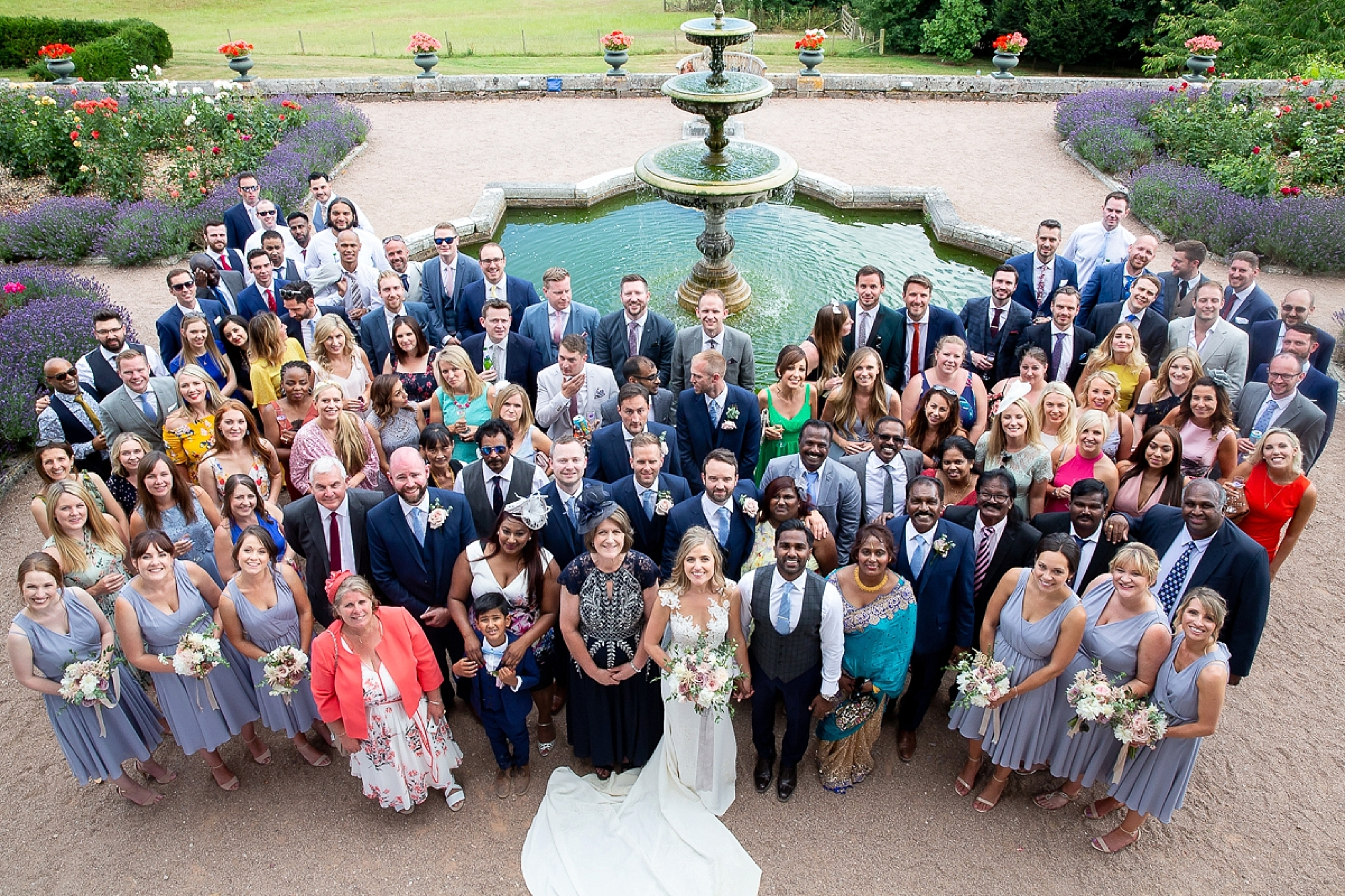 Group shot of wedding at Pynes House in Devon from above as guests surround water fountain