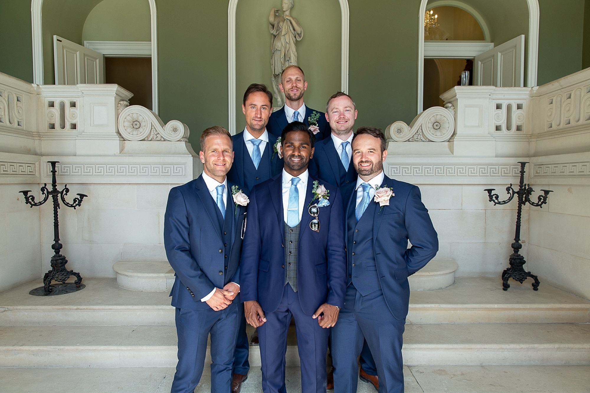 Groom and groomsmen stand in the entrance of Pynes House in Devon wedding