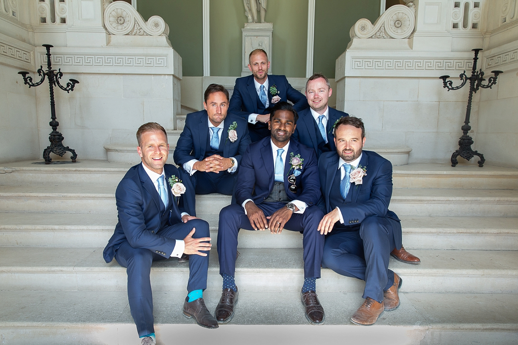 Groom and groomsmen stand in the entrance of Pynes House at Devon wedding