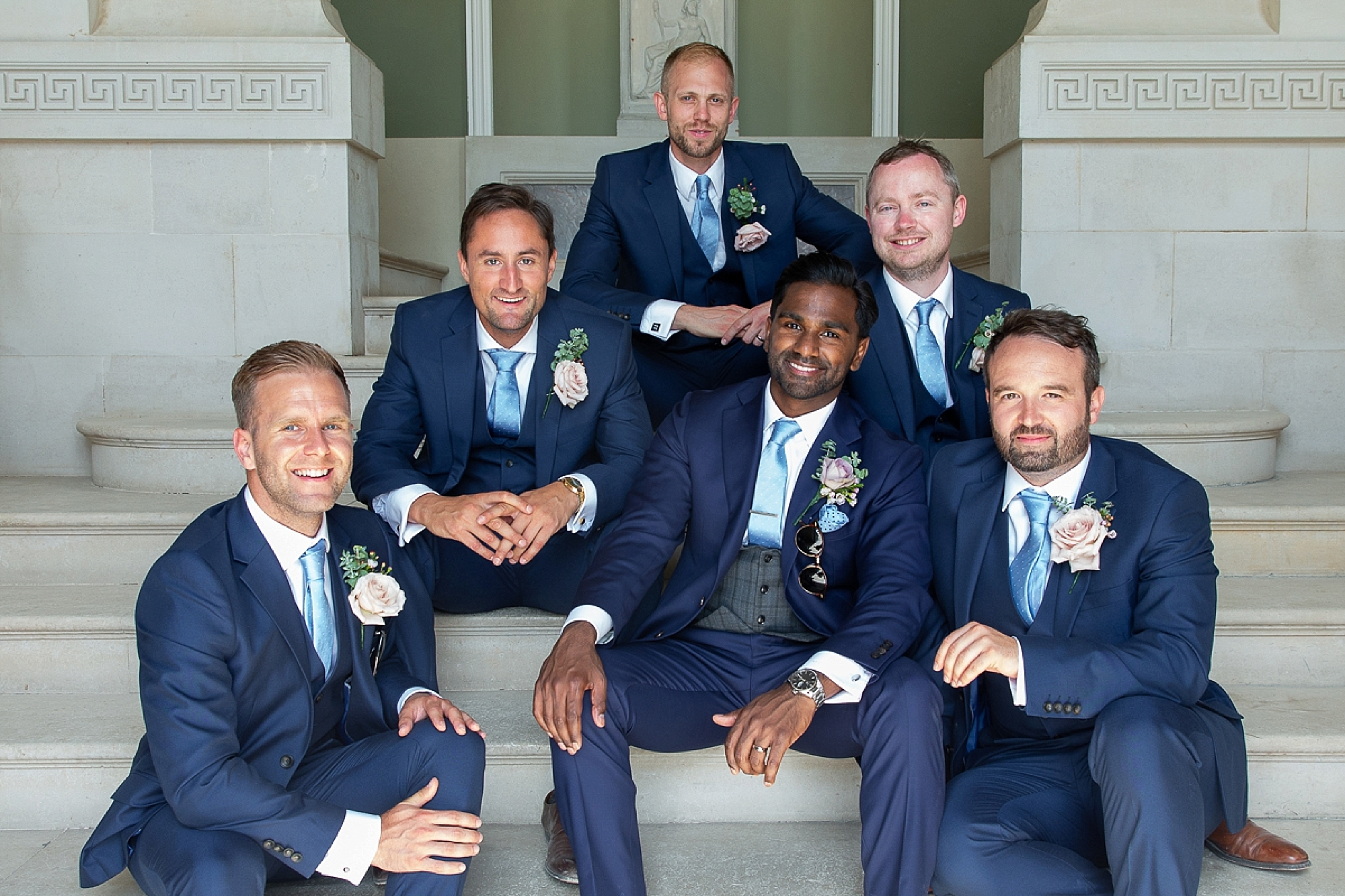 Groom and groomsmen sit on the steps in the entrance of Pynes House in Devon wedding