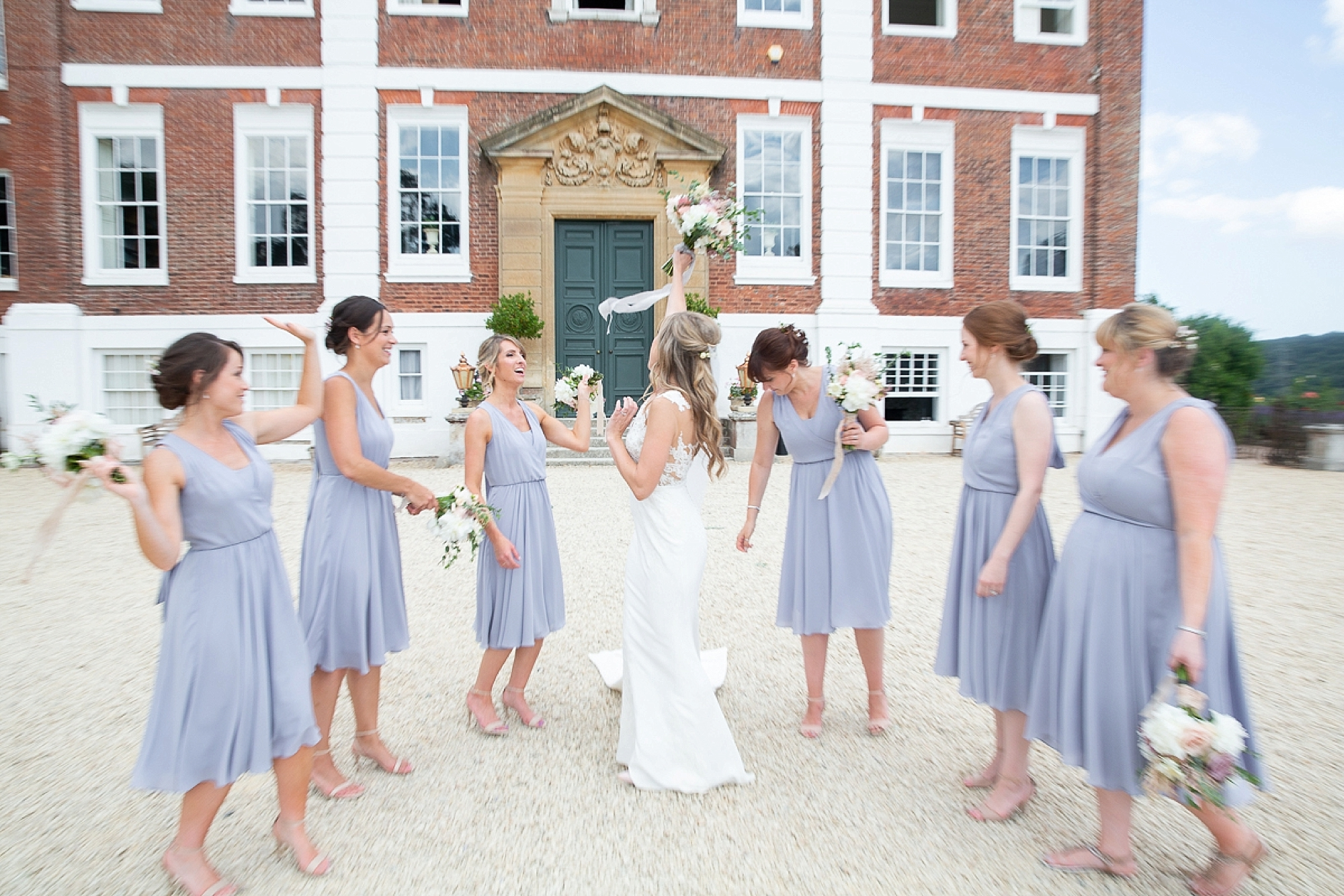 Bride in pronovias dress stands holding bouquet up at Devon wedding surrounded by her bridesmaids in blue