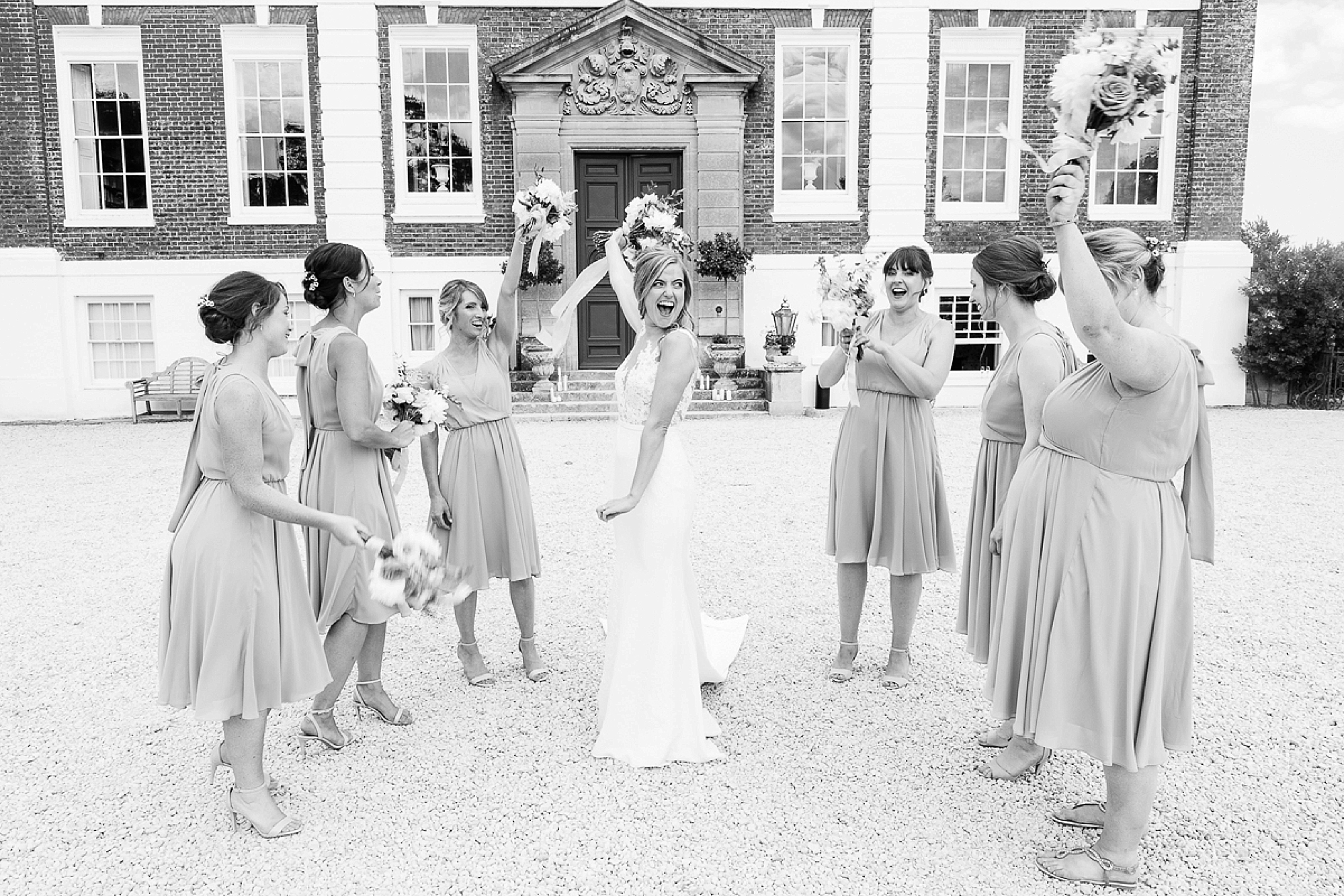 Bride in pronovias dress stands holding bouquet up laughing at Devon wedding surrounded by her bridesmaids