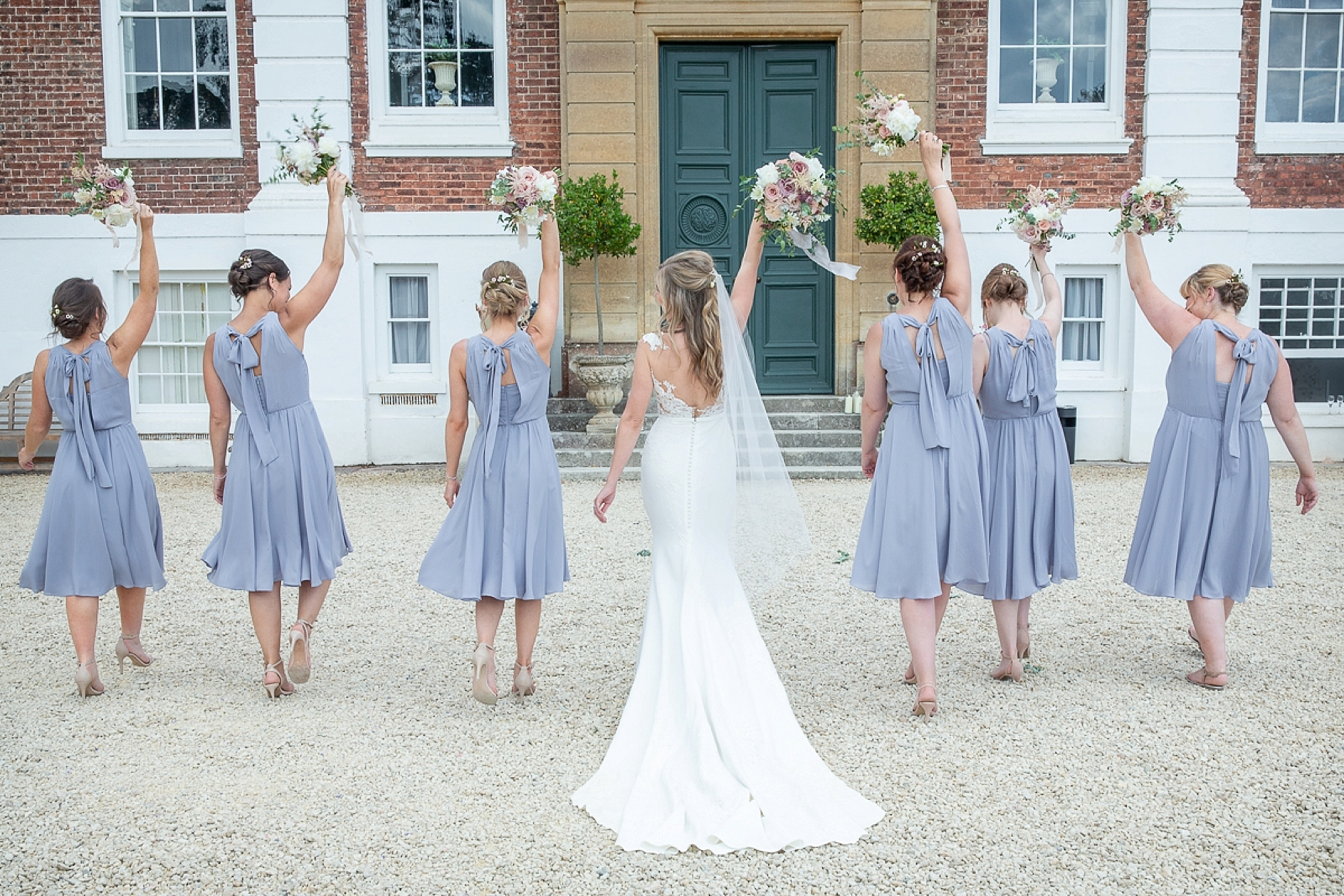 Bride in pronovias dress and her bridesmaids hold bouquets up at Devon wedding at Pynes House