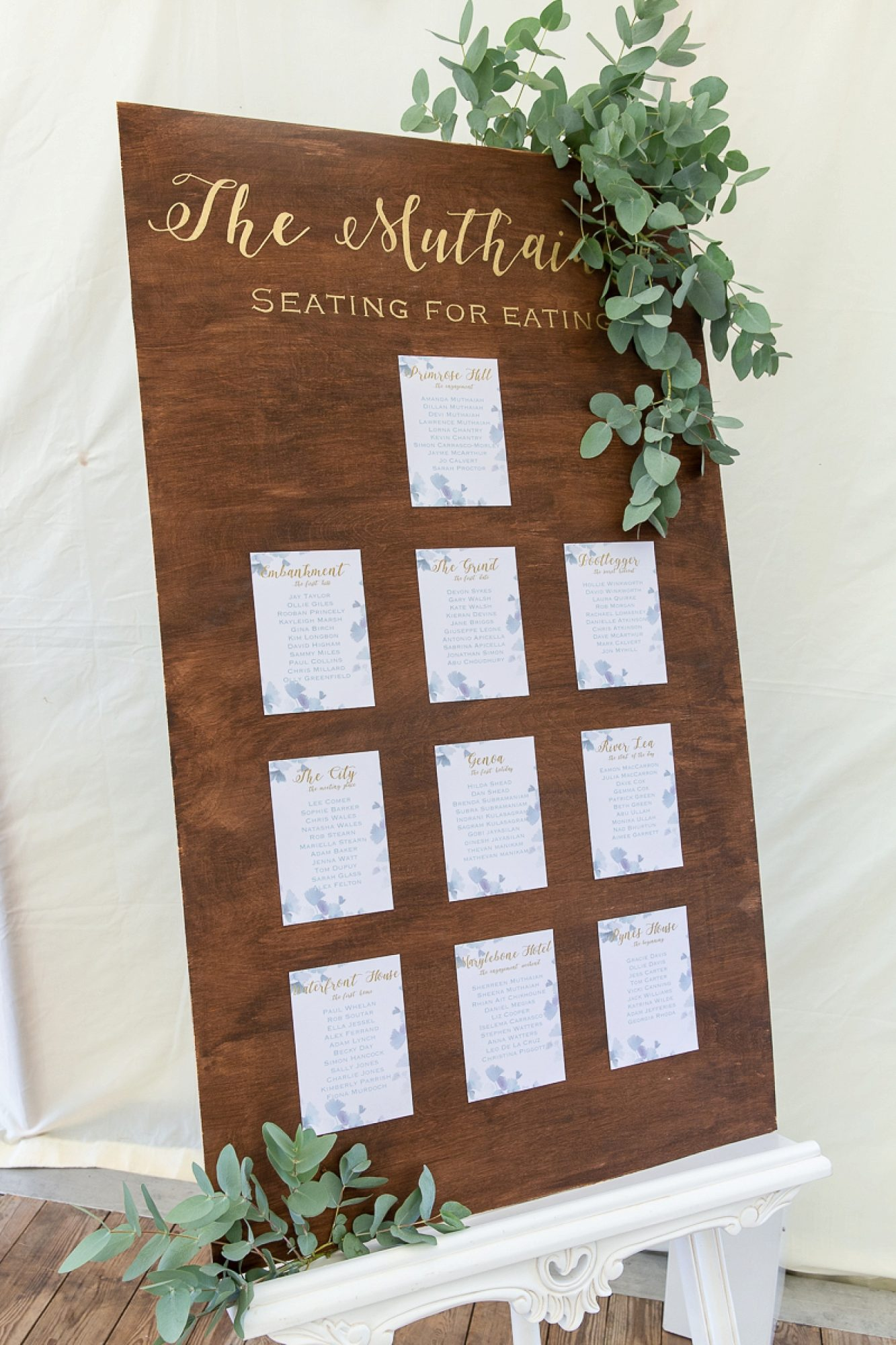 Dark wooden table plan with eucalyptus leaf hanging down on the right side