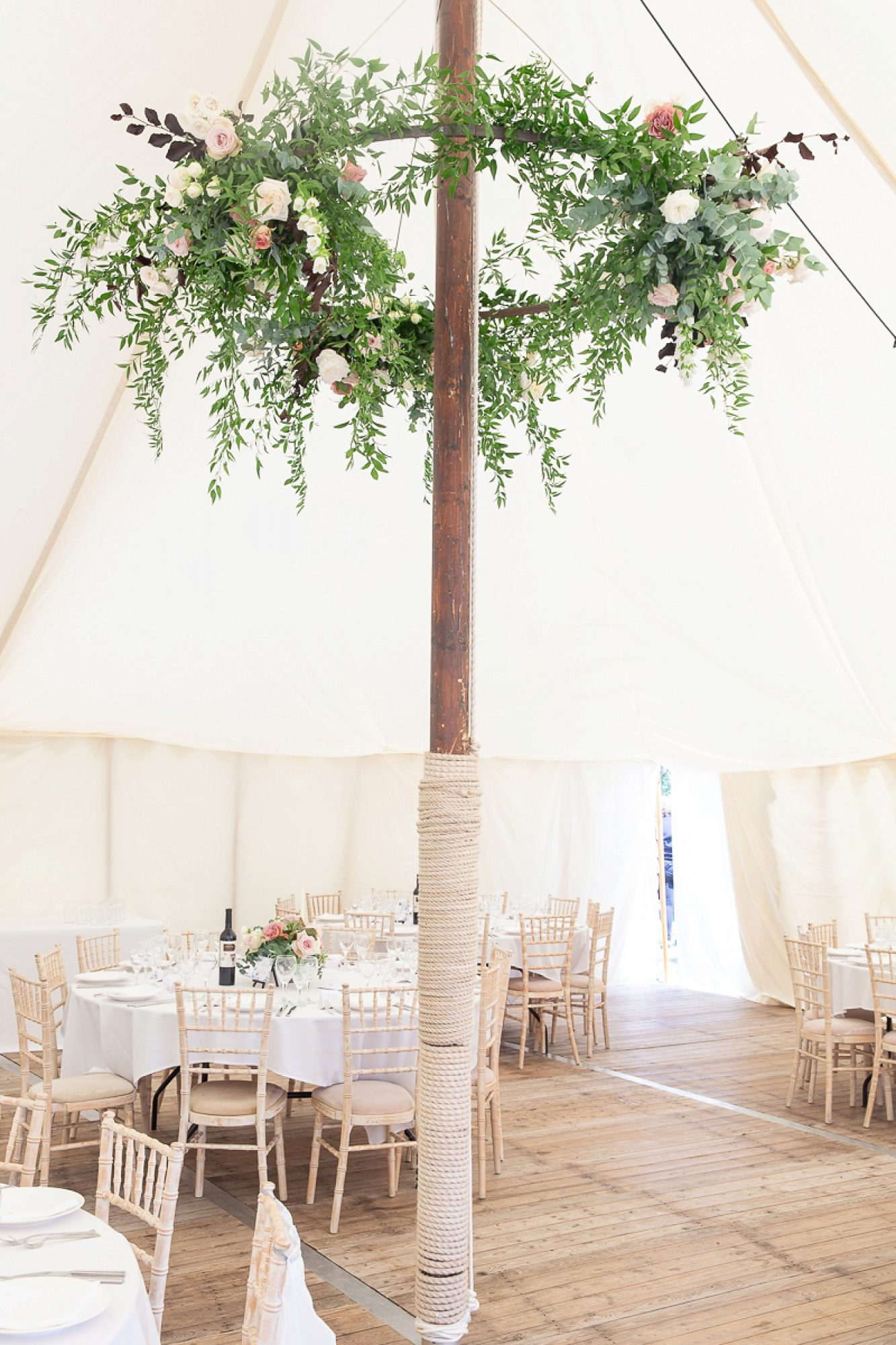 pole at the centre of a wedding marquee in devon wedding with large floral circular display