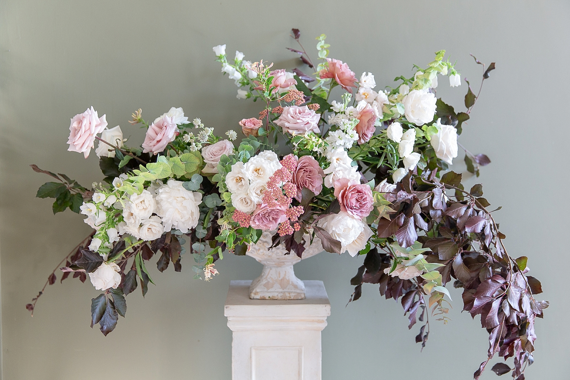 large floral display in a giant urn with pink, white flowers and auburn leaves