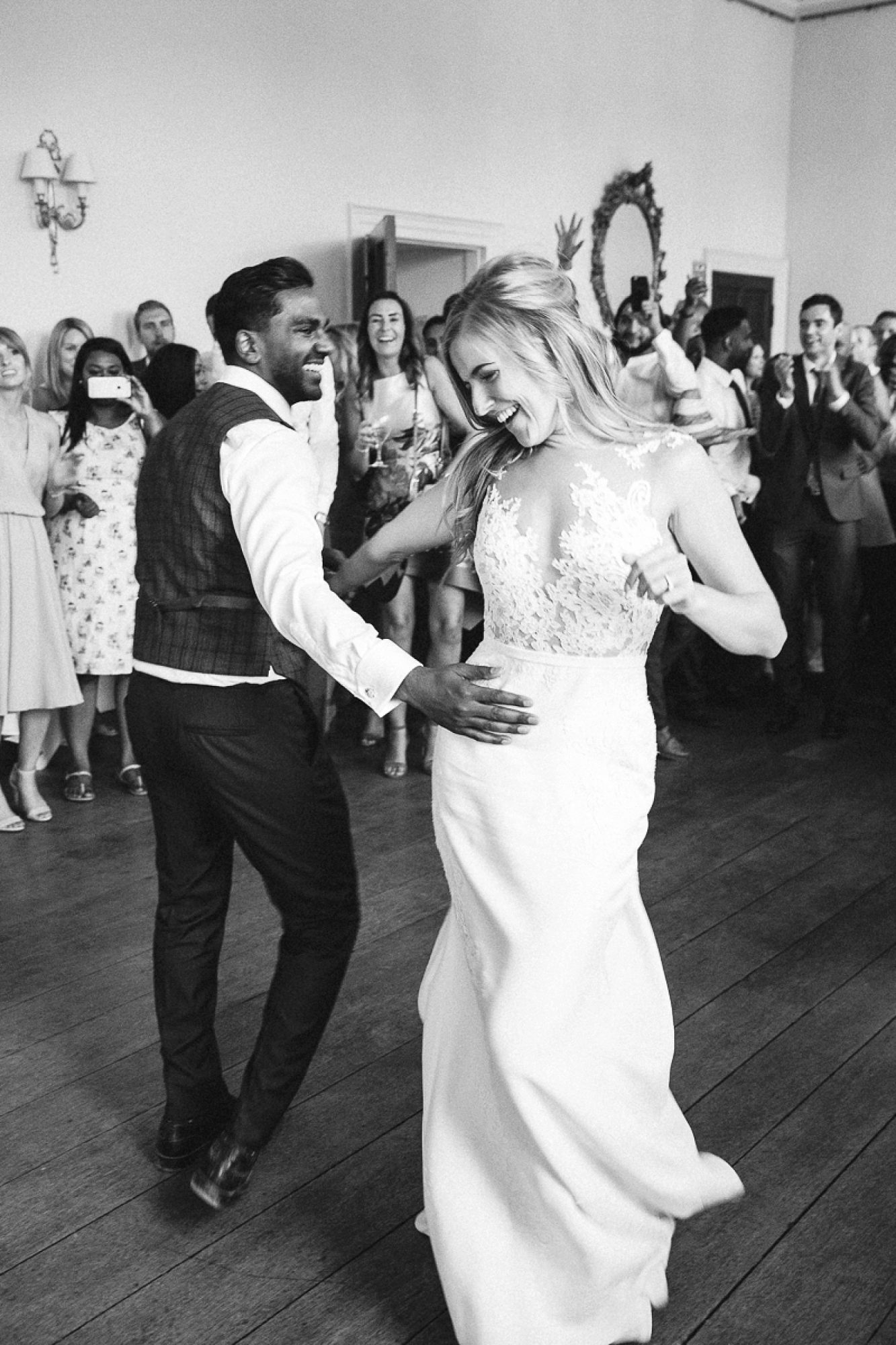 bride and groom dancing and laughing as they spin at Pynes house wedding in black and white