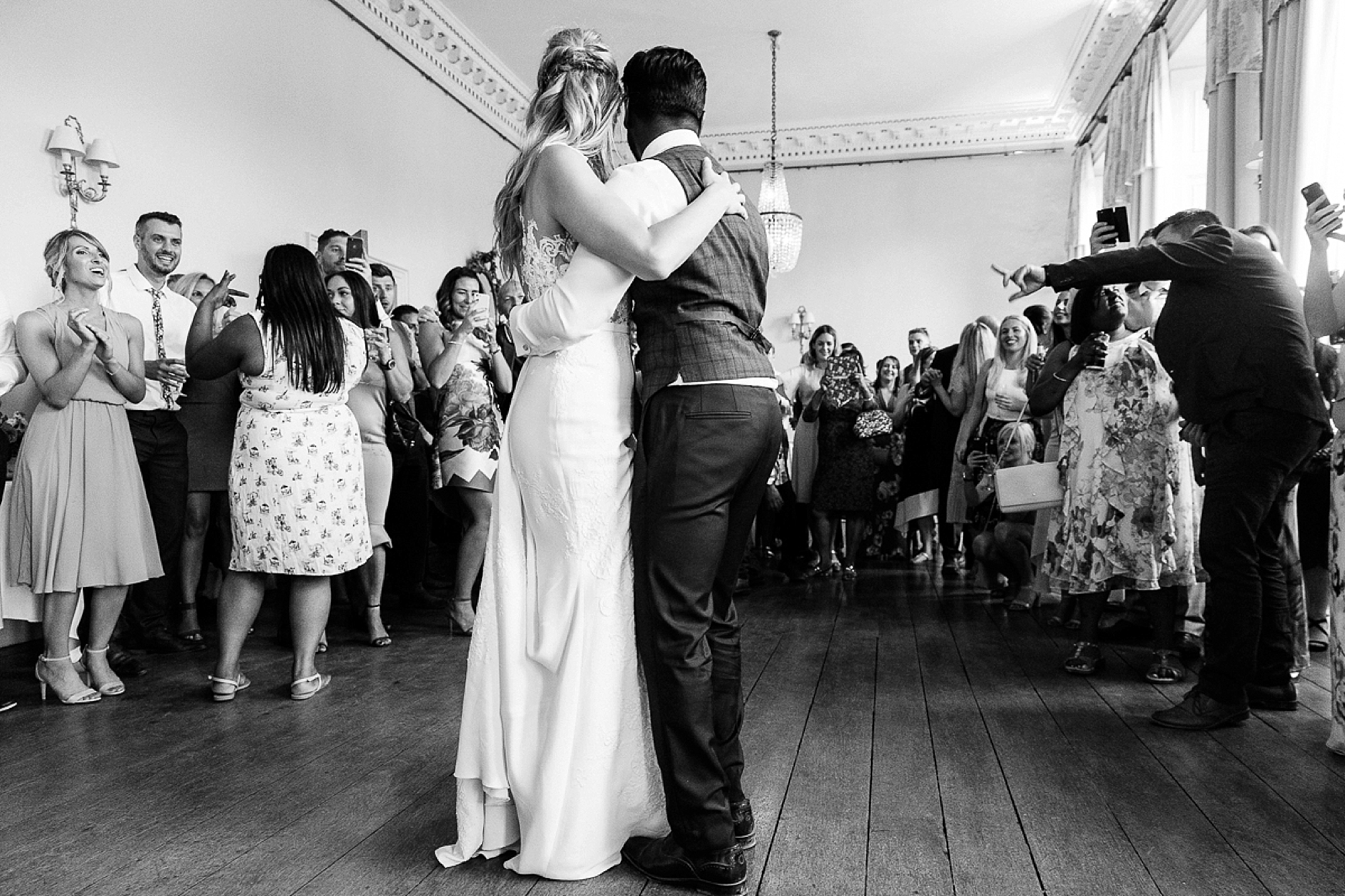 bride and groom finish their first dance in the ballroom at Pynes house as their guests watch