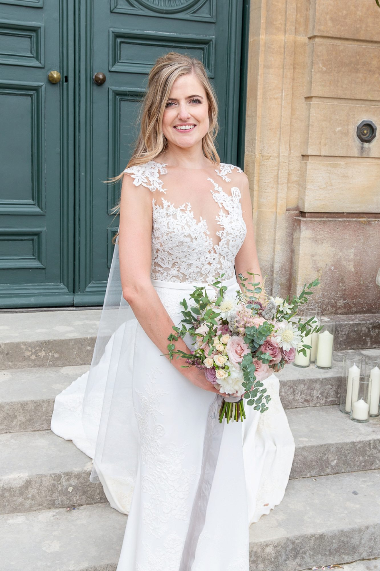 bride in pronovias wedding gown stands on the steps of Pynes house with her wedding bouquet
