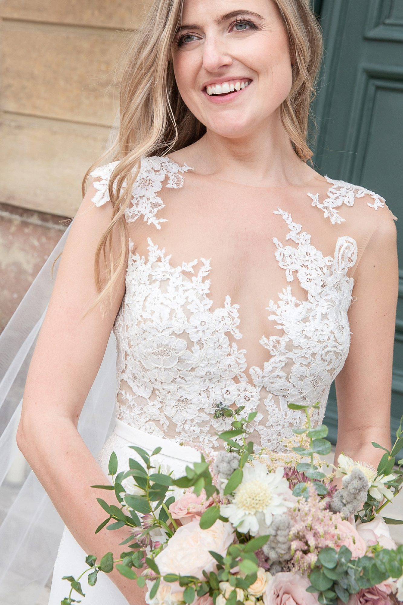 bride wearing pronovias lace dress laughs with her bouquet at Pynes house