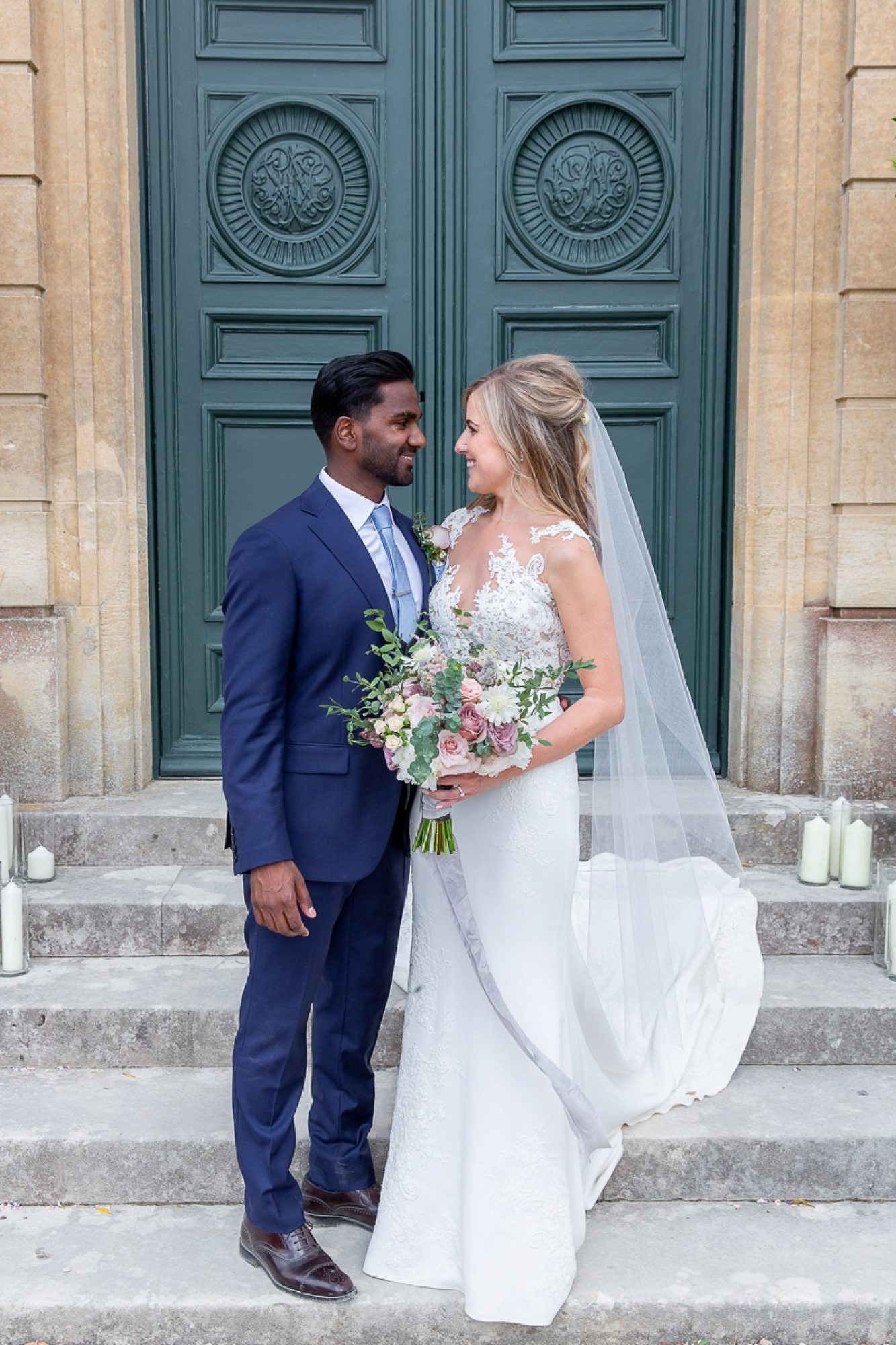 bride in pronovias wedding gown and groom in blue suit look at each other at the entrance of Pynes house