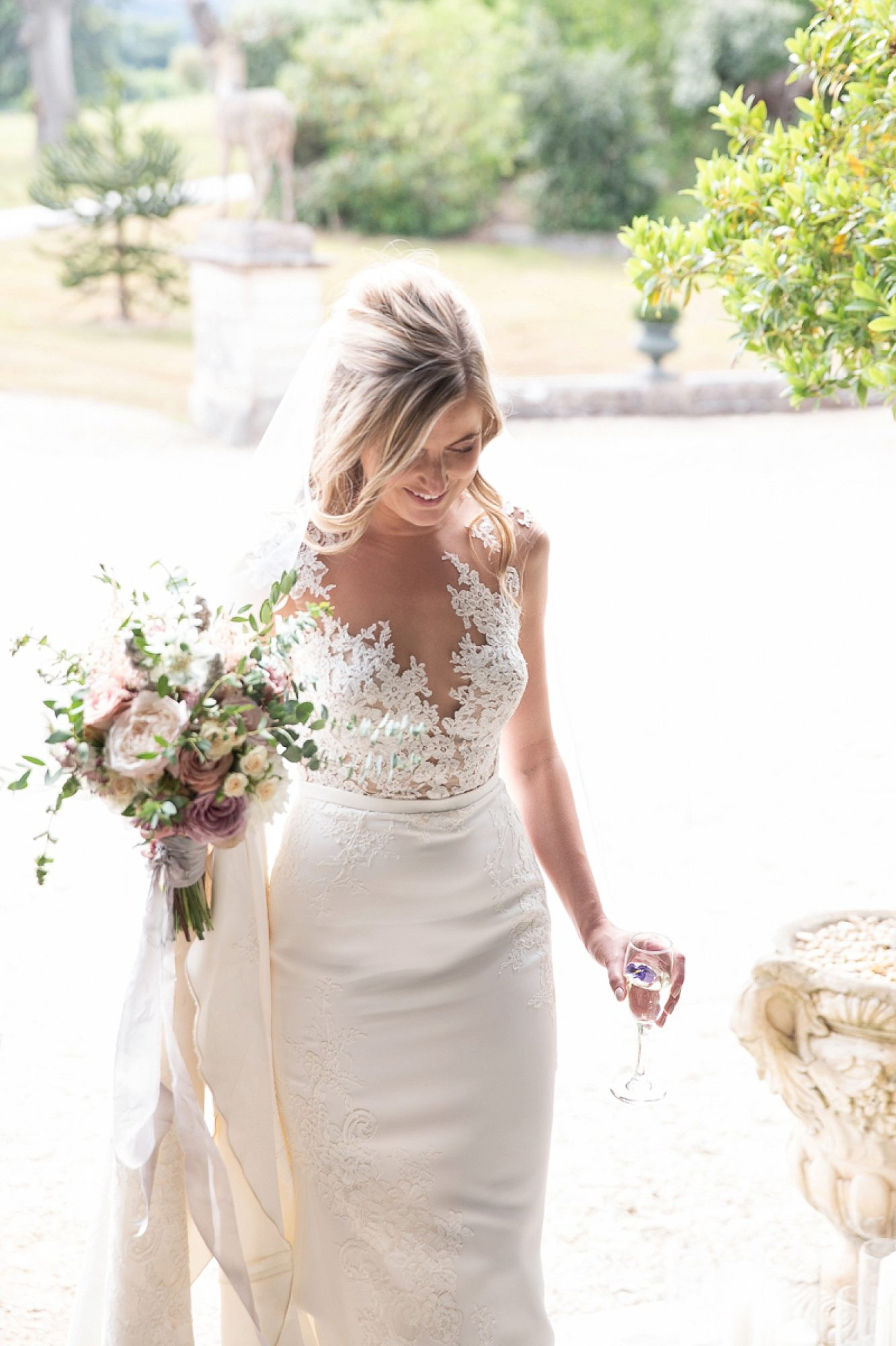 bride holding champagne and wedding bouquet enters Pynes House in pronovias wedding dress