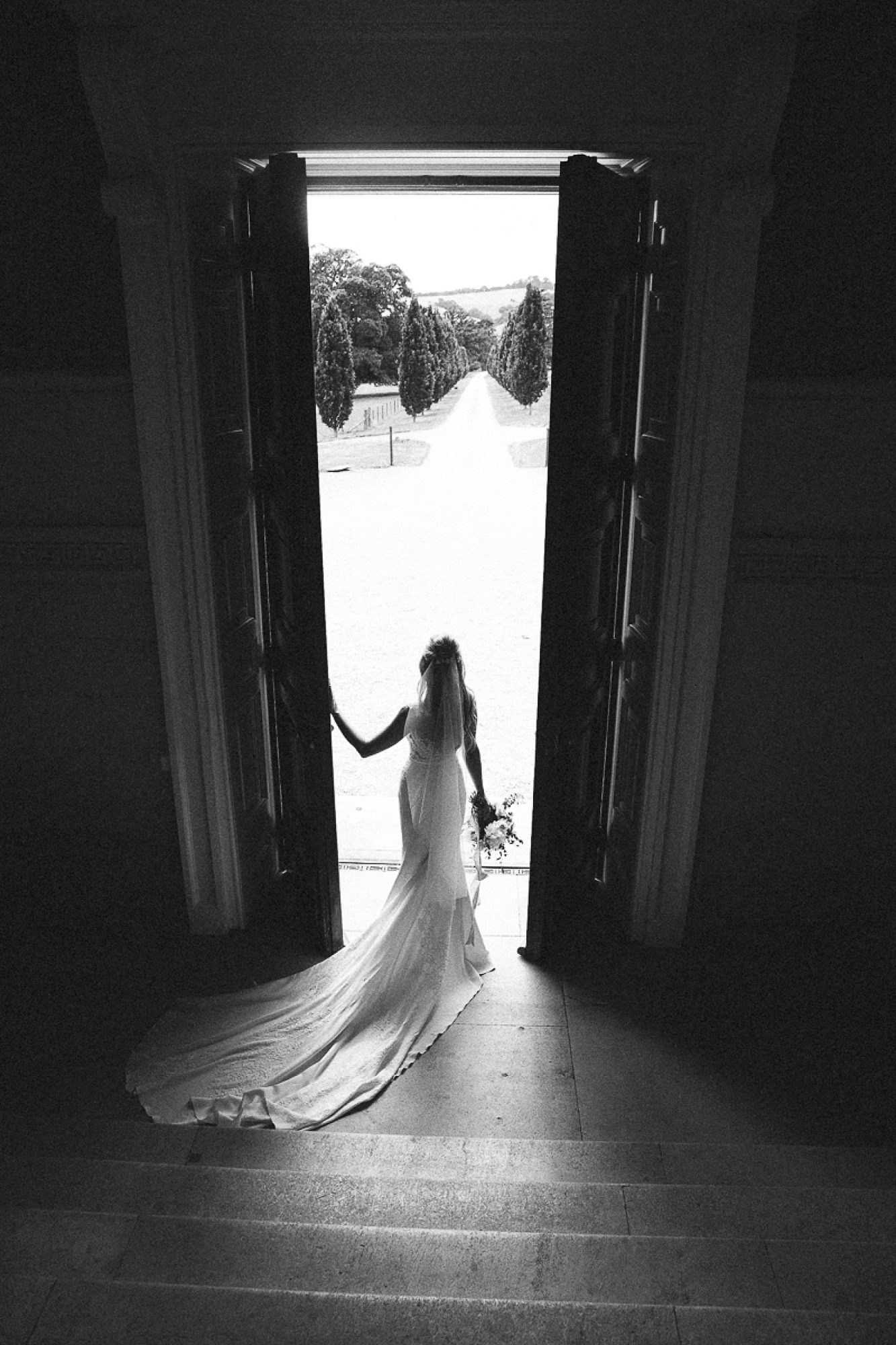 Bride in pronovias dress stands holding the giant front door at Pynes house