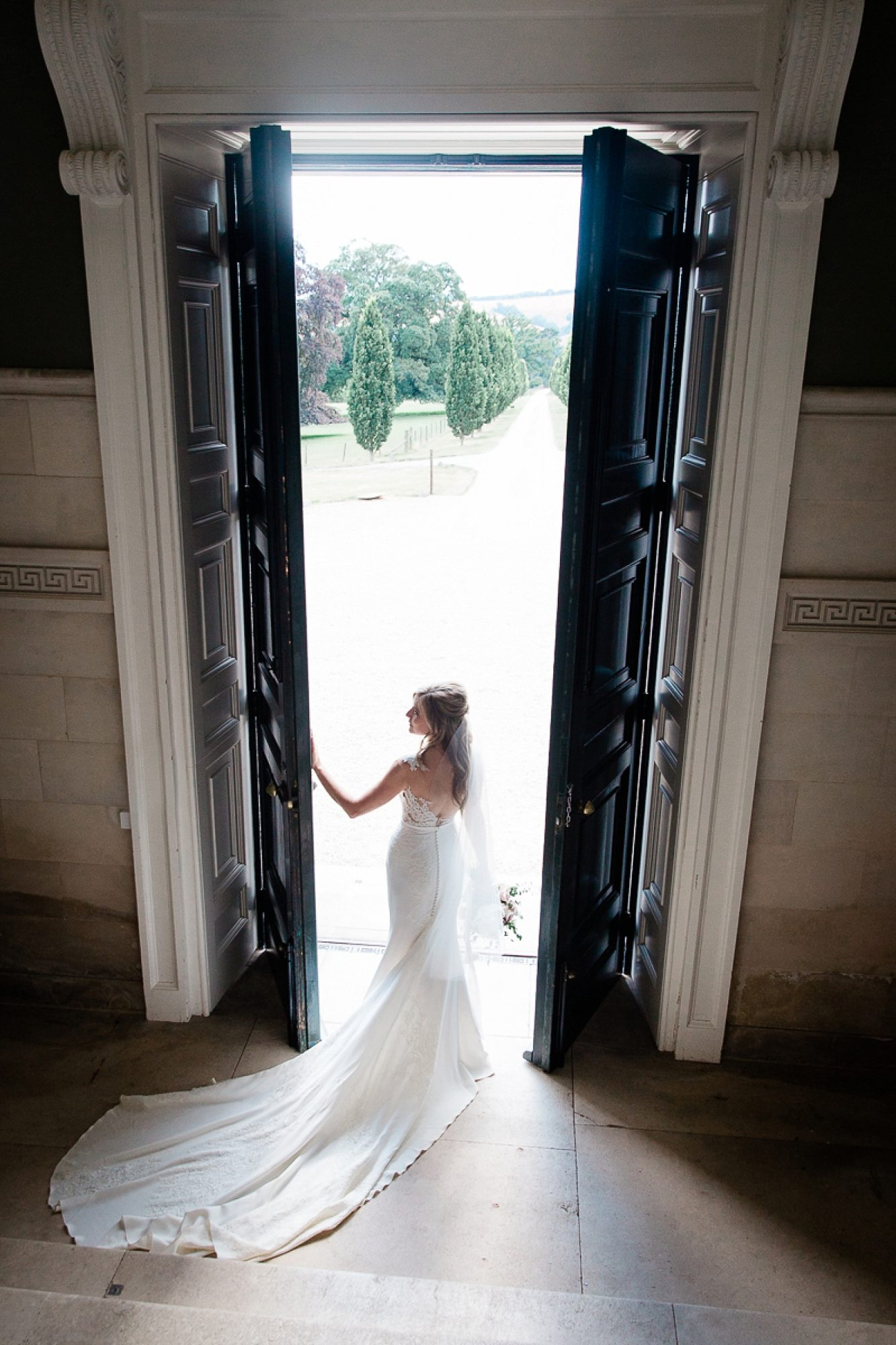 Bride in pronovias dress stands holding the giant front door at Pynes house wedding