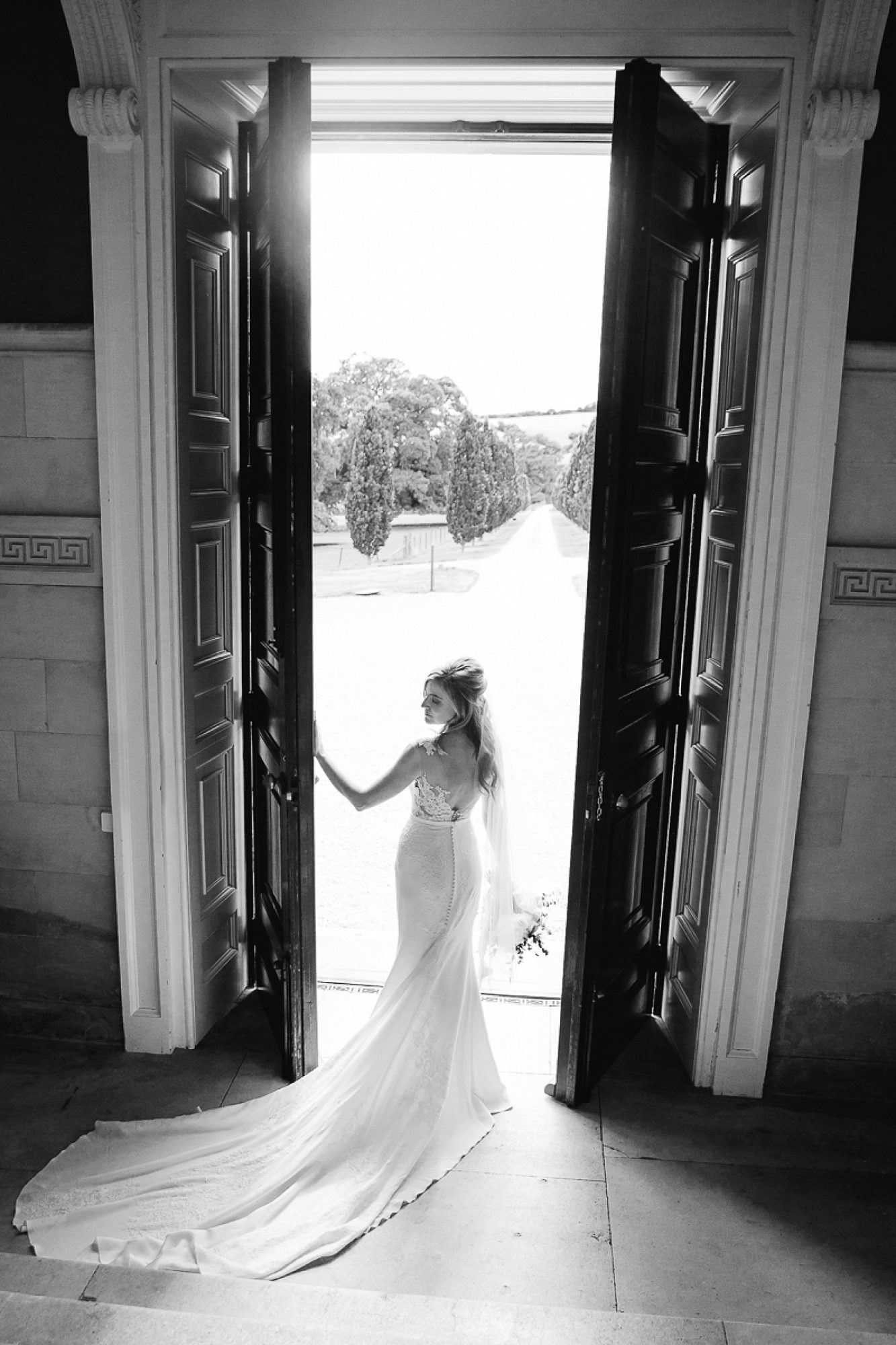 Bride in pronovias dress stands holding the giant front door at Pynes house wedding in devon