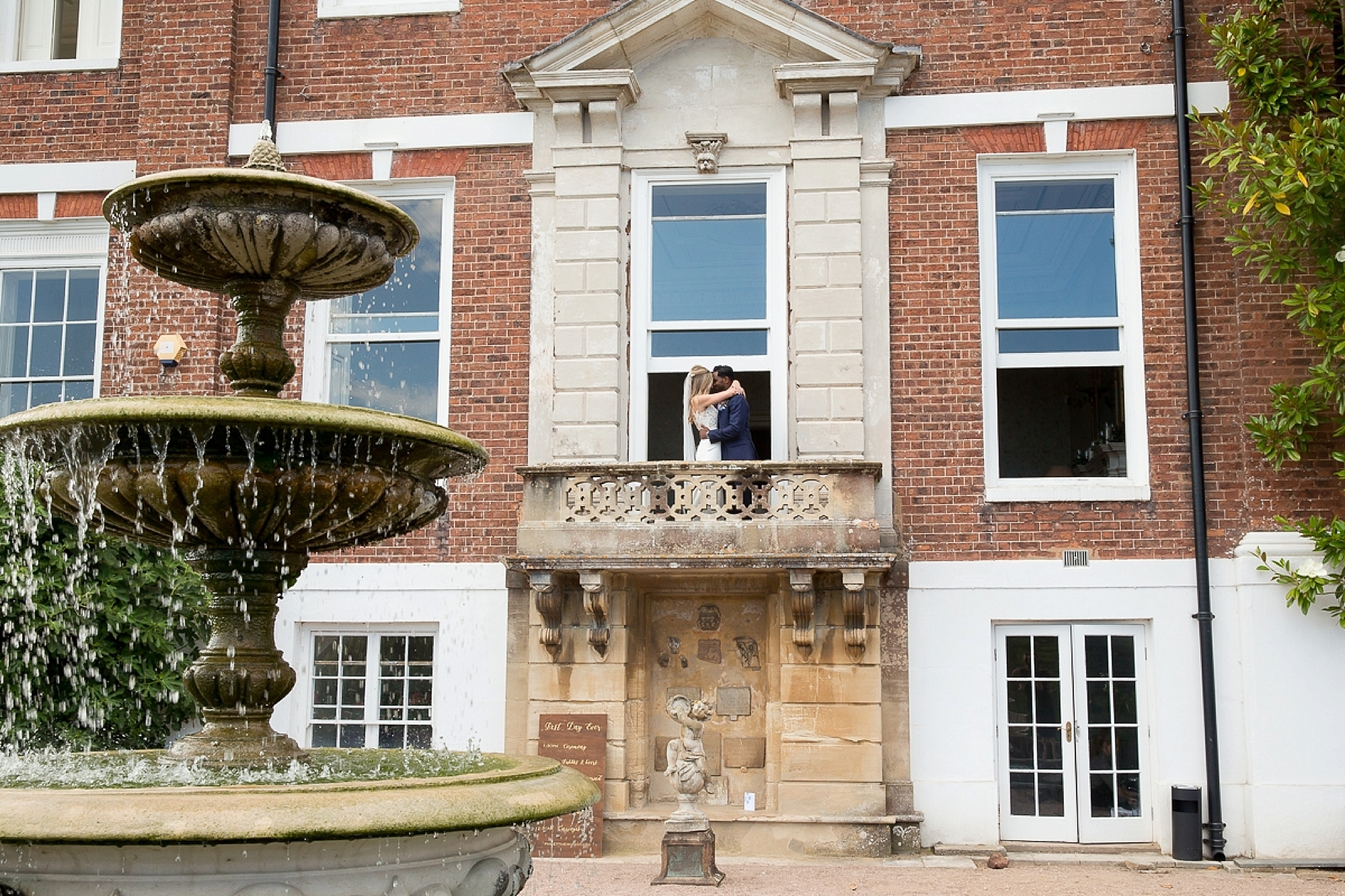 bride and groom kiss on the balcony of their Pynes house wedding in devon