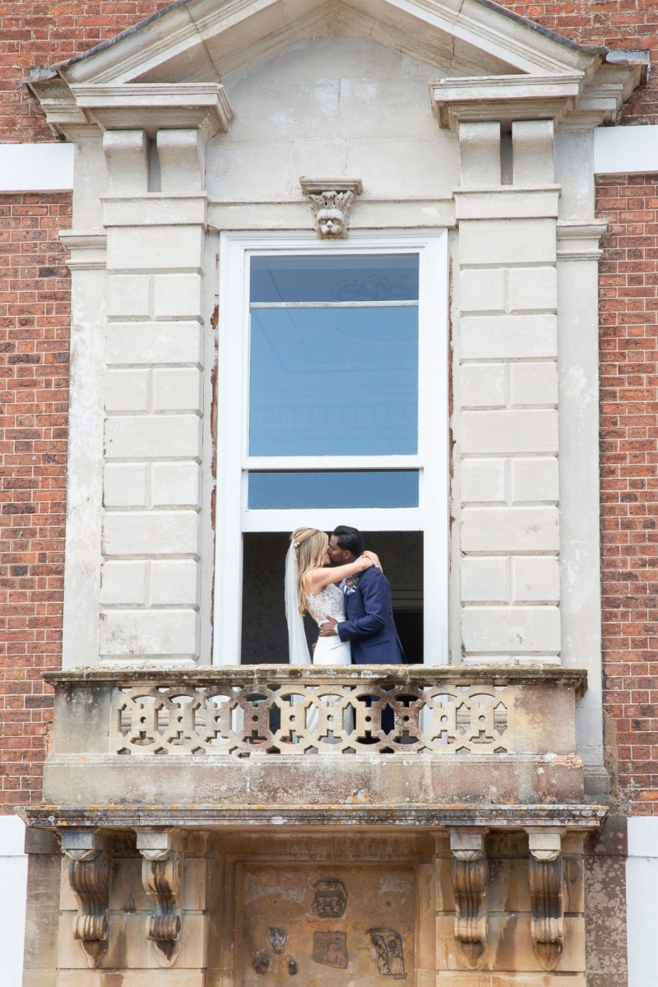 bride and groom kiss on the balcony of Pynes house at their devon wedding