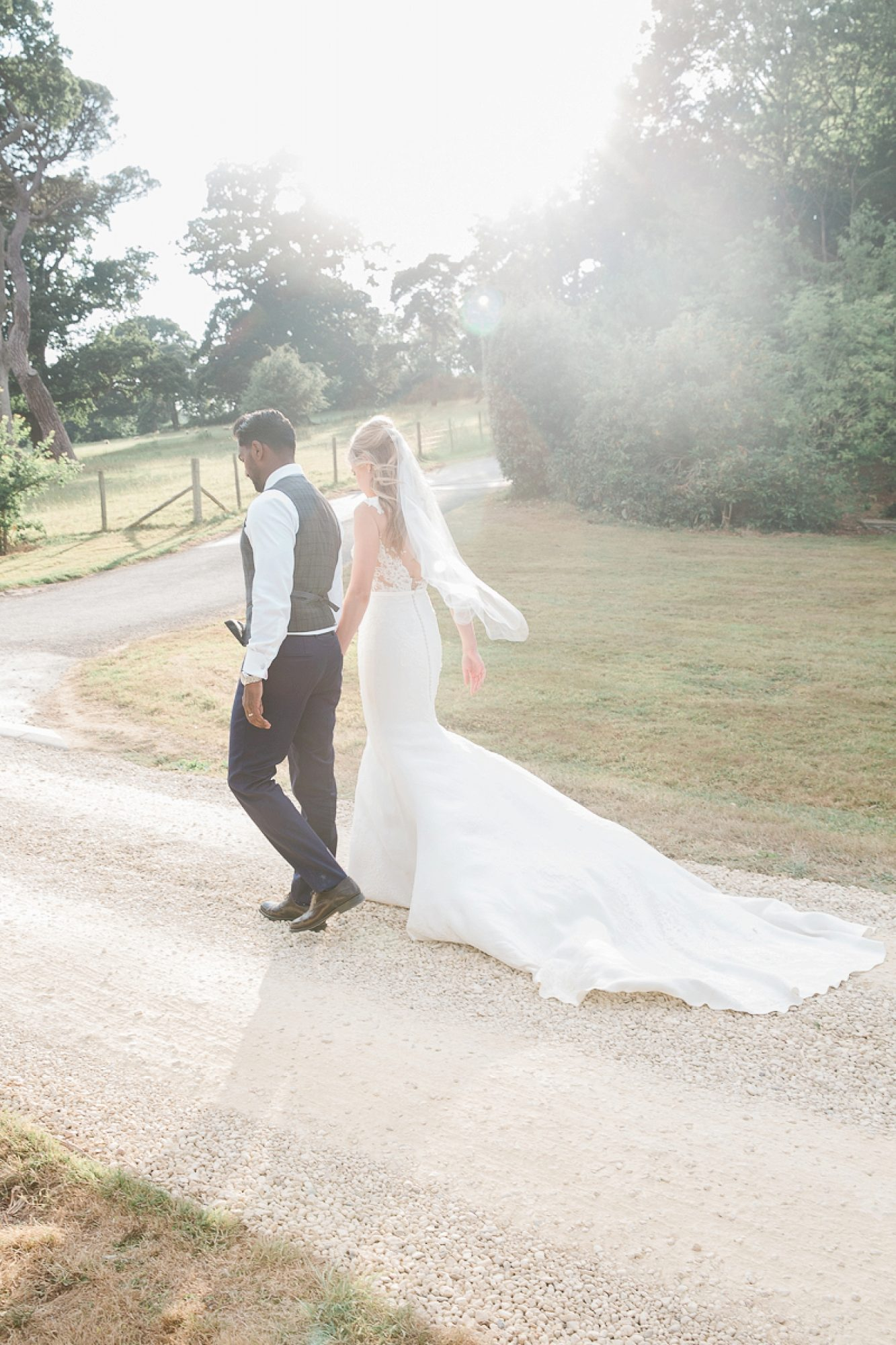 bride and groom walk in to the sun holding hands at their devon wedding