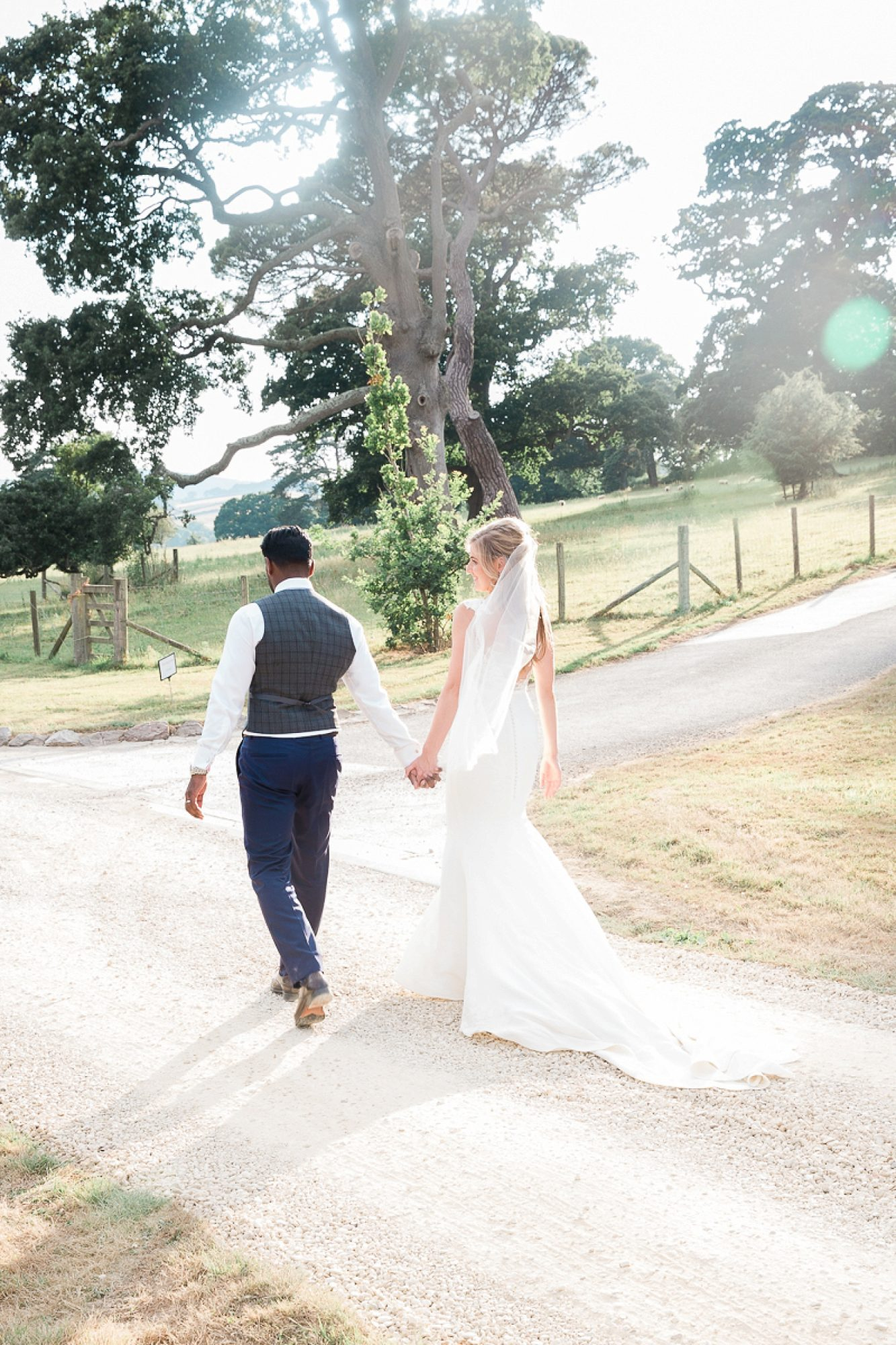 bride and groom walk in to the gardens of Pynes House as the sun sets holding hands at their devon wedding