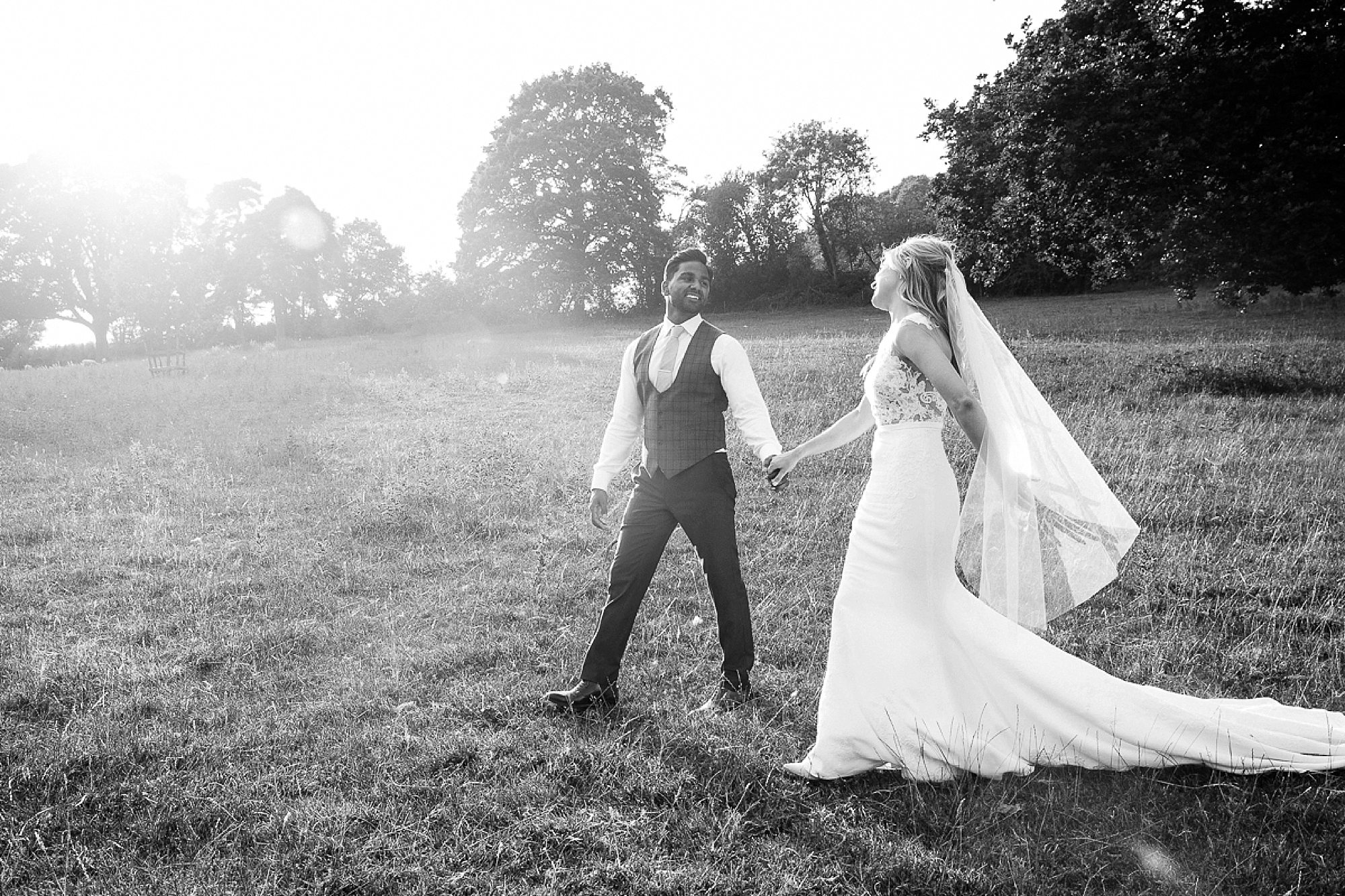 bride and groom look and laugh at each other as they walk in the sun