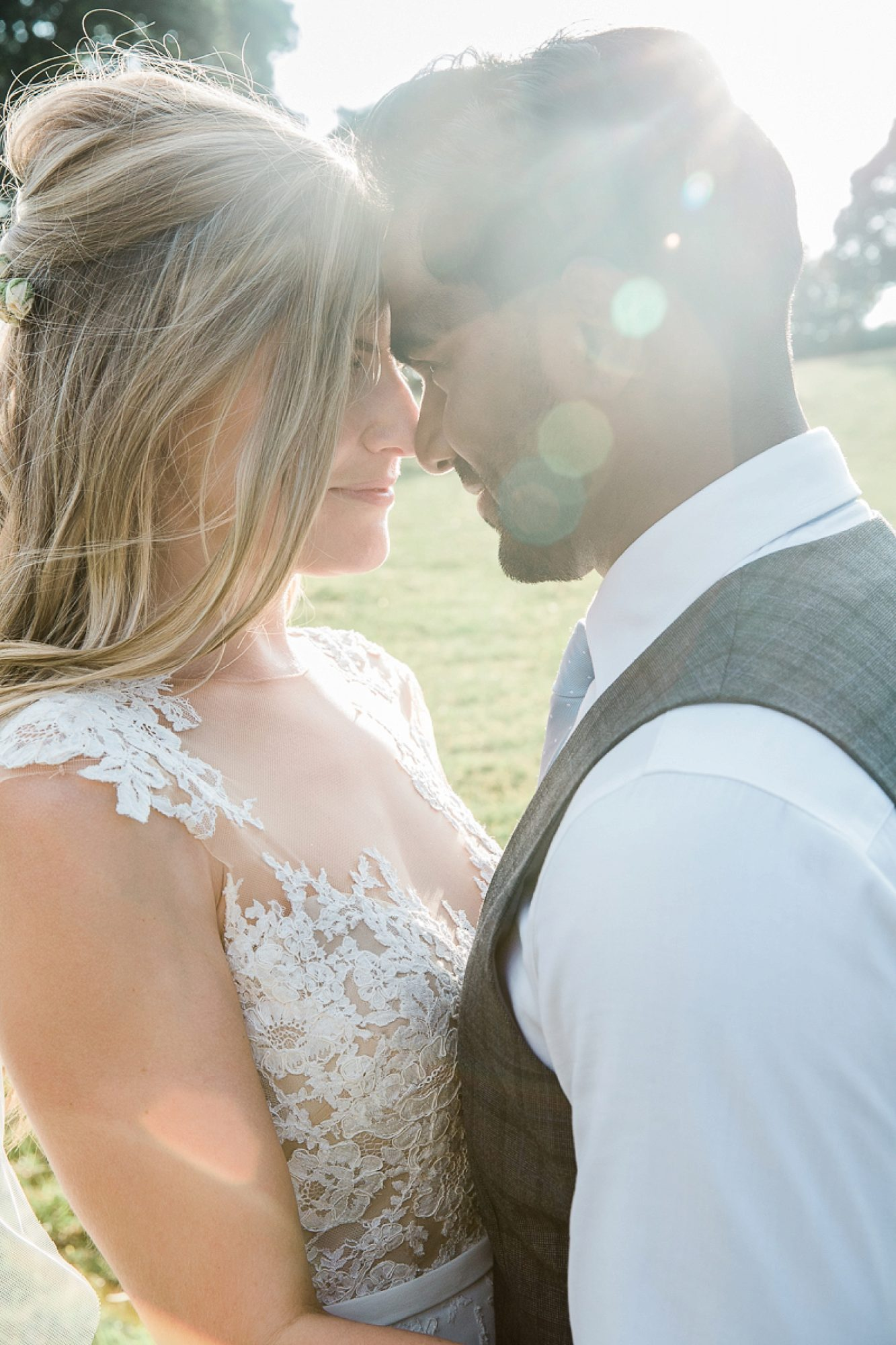 the sun refracts as a couple embrace in the gardens of their devon wedding