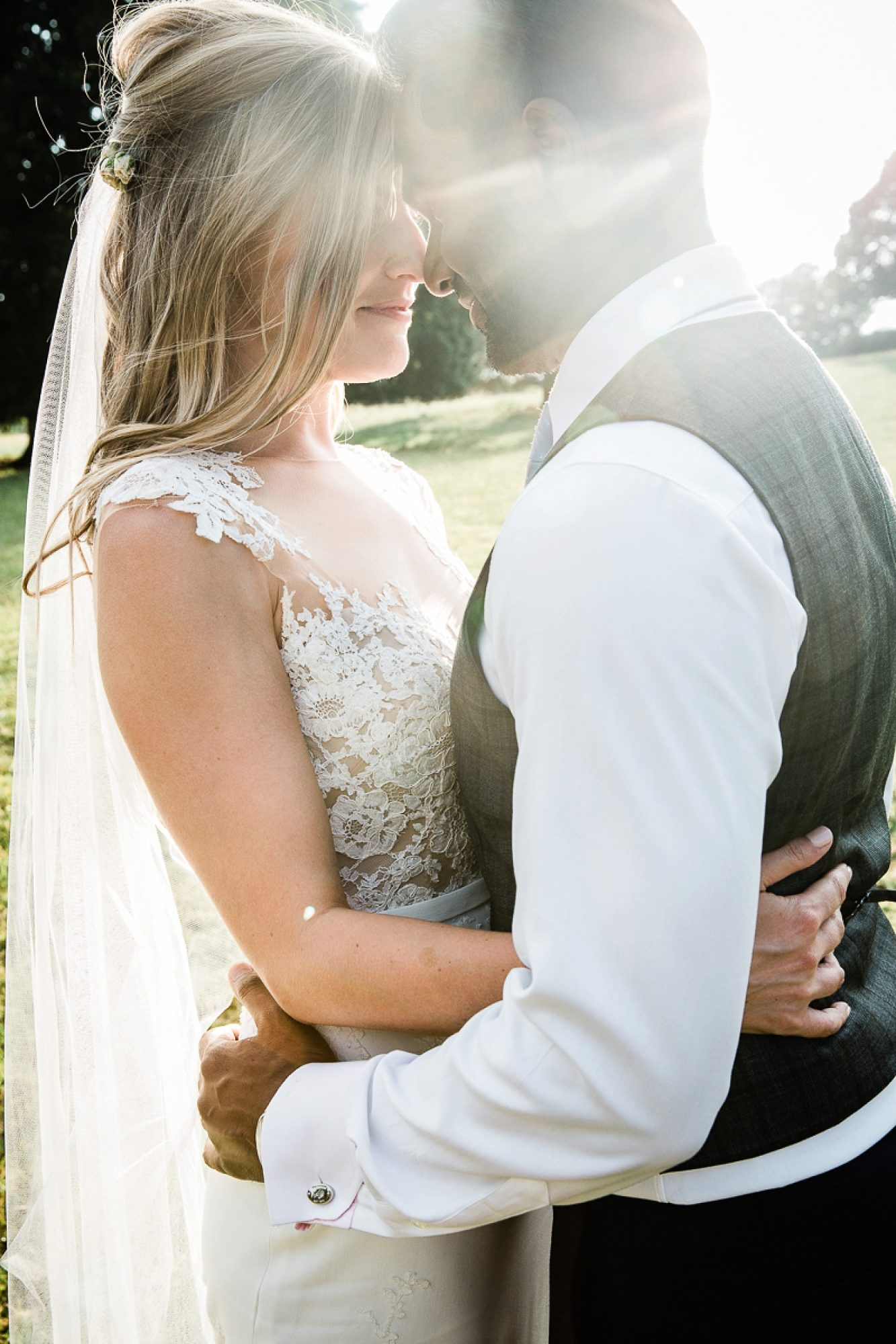 the sun refracts as a couple embrace in the gardens of their Pynes house wedding