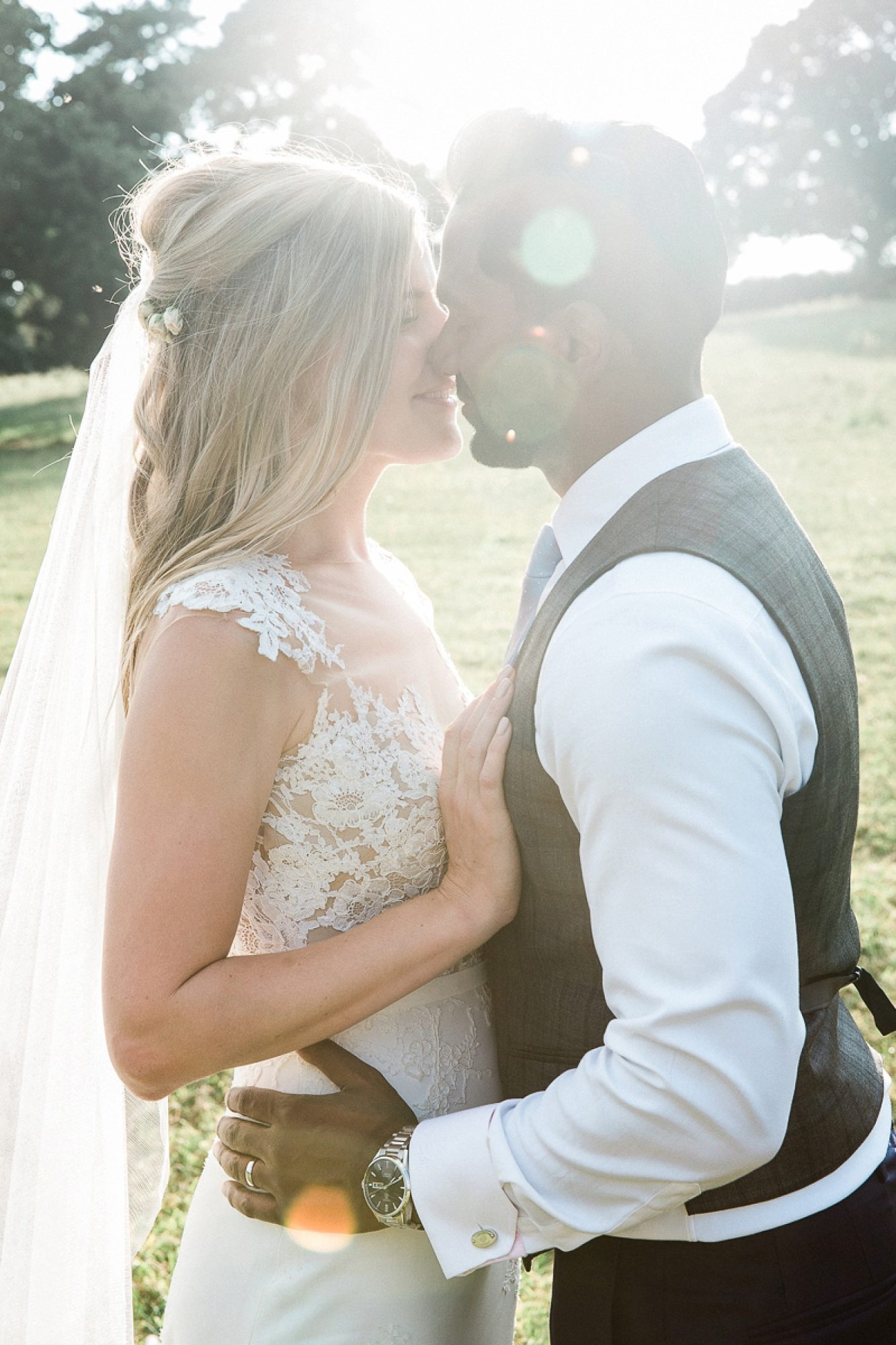the sun refracts behind a couple as they kiss in the gardens of their devon wedding