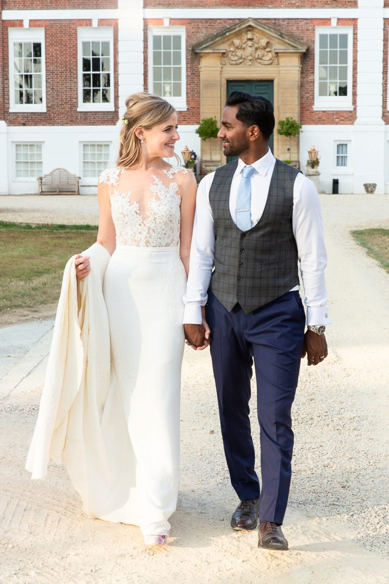 Bride and groom look towards each other as they walk holding hands with Pynes house behind them