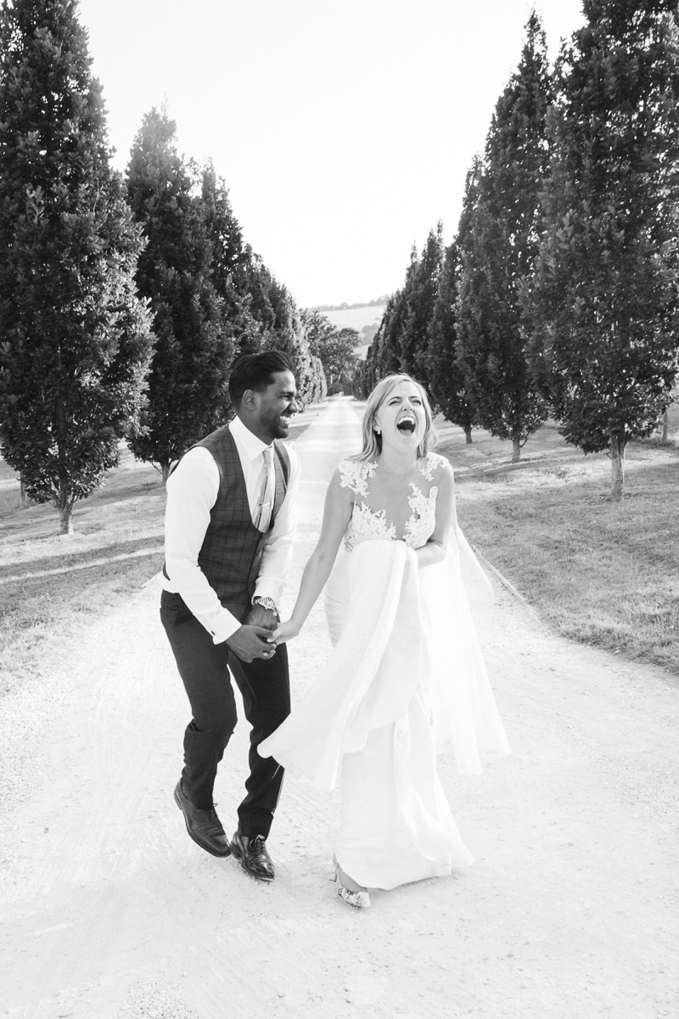 Bride laughs hysterically as her husband holds her hand on the drive of Pynes house