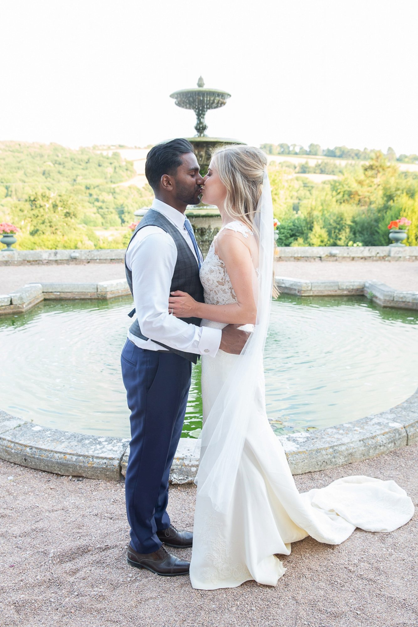 wedding couple kiss in front of the fountain at Pynes house in devon