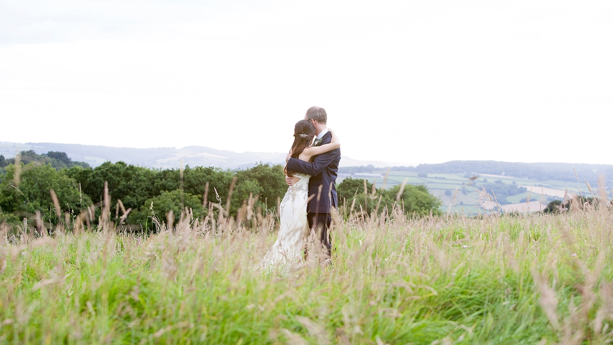 couple embrace in a field at sunset at river cottage in devon