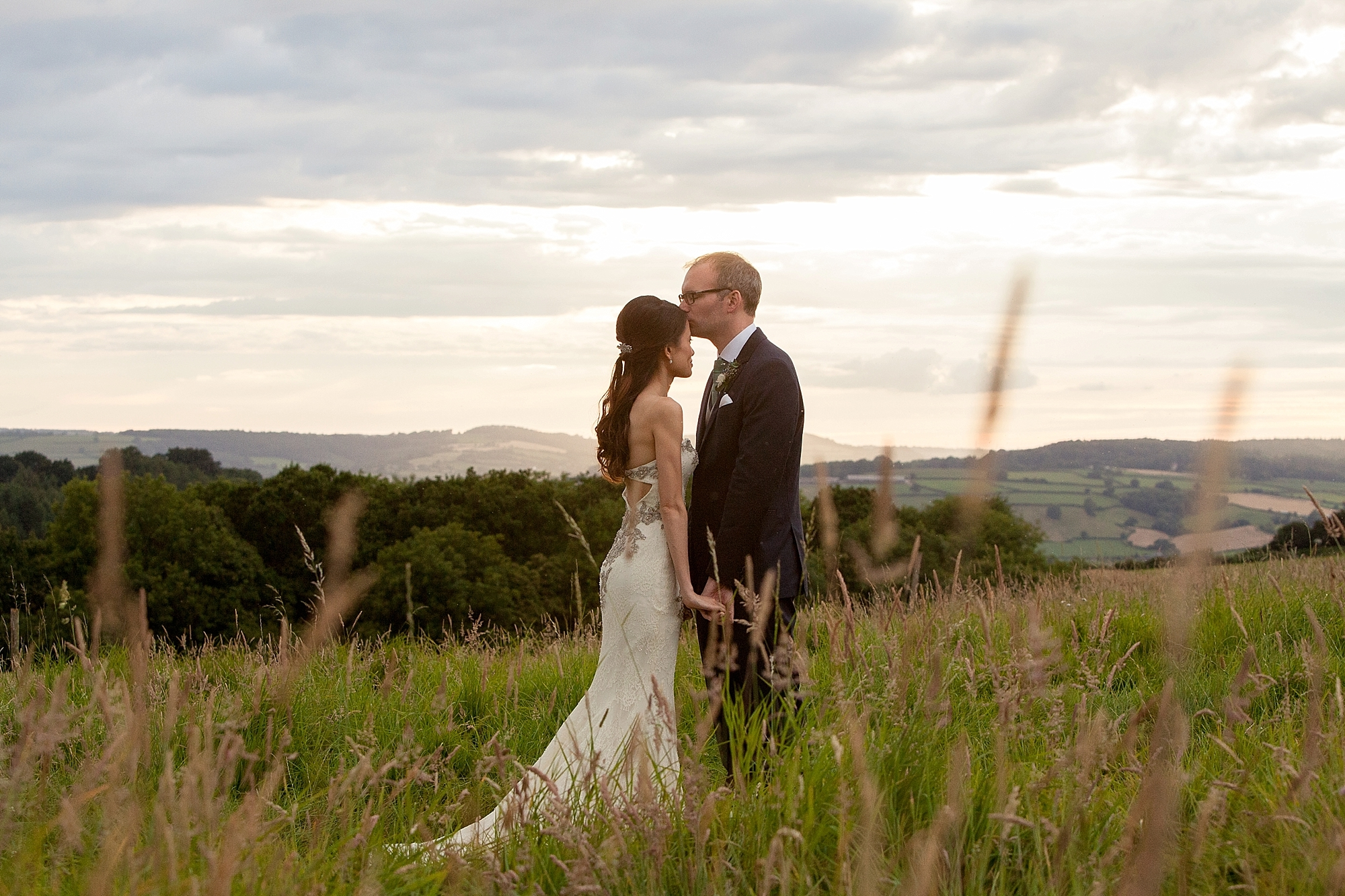 groom kisses bride's head in a field at sunset at river cottage in devon