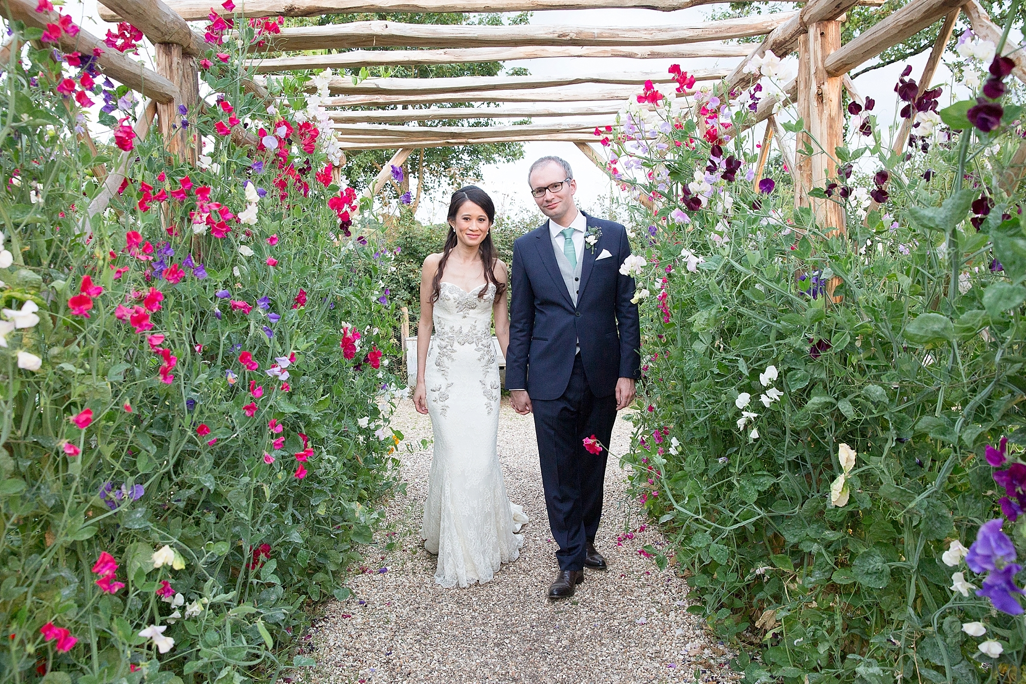 wedding couple walk through an archway filled with sweet-peas at River Cottage