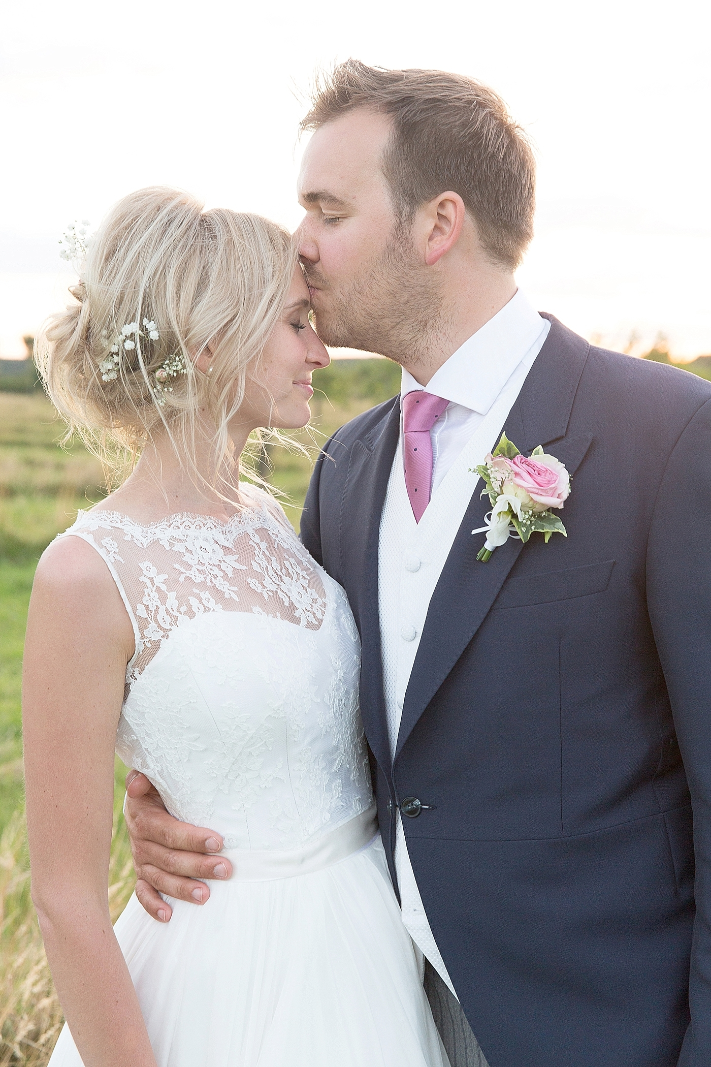 groom kisses brides head at wedding at Lyveden New Bield