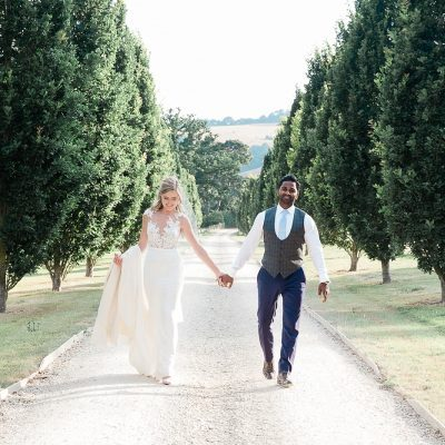 bride and groom walk holding hands in a tree lined driveway of Pynes House