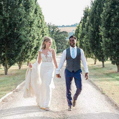 bride and groom walk as they hold hands in a tree lined driveway of Pynes House