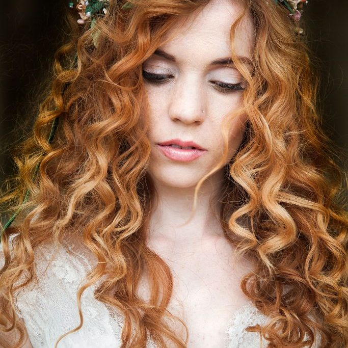 bride with red curly hair and a luxury flower crown
